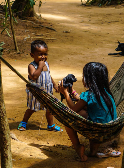 Cambodian Girl Cambodian Life Bonding Boys Cambodian Children Casual Clothing Child Childhood Day Family Full Length Girls Hammock Leisure Activity Lifestyles Outdoors Pet Puppy Real People Sand Sitting Togetherness Young Adult Young Women