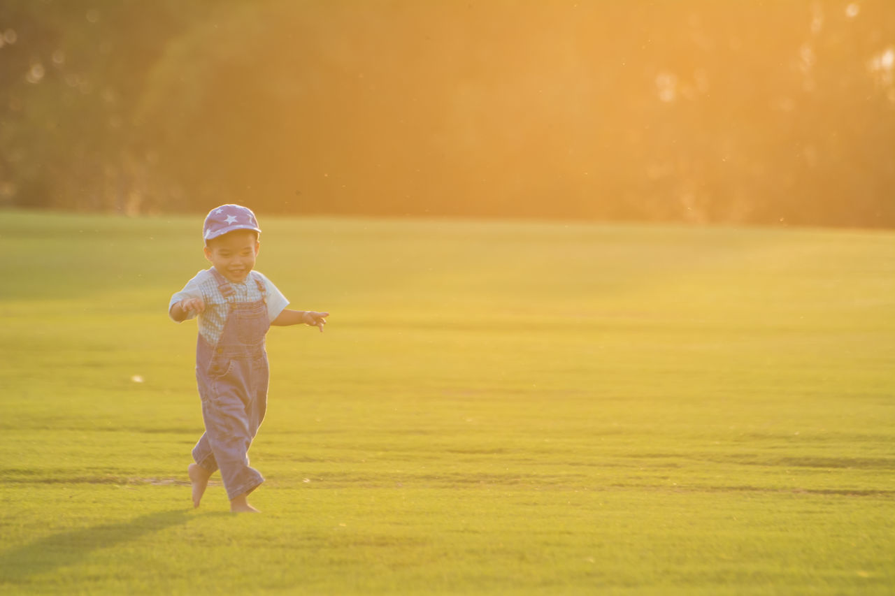 real people, childhood, one person, leisure activity, sunset, boys, elementary age, lifestyles, field, outdoors, full length, nature, playing, grass, girls, day, people