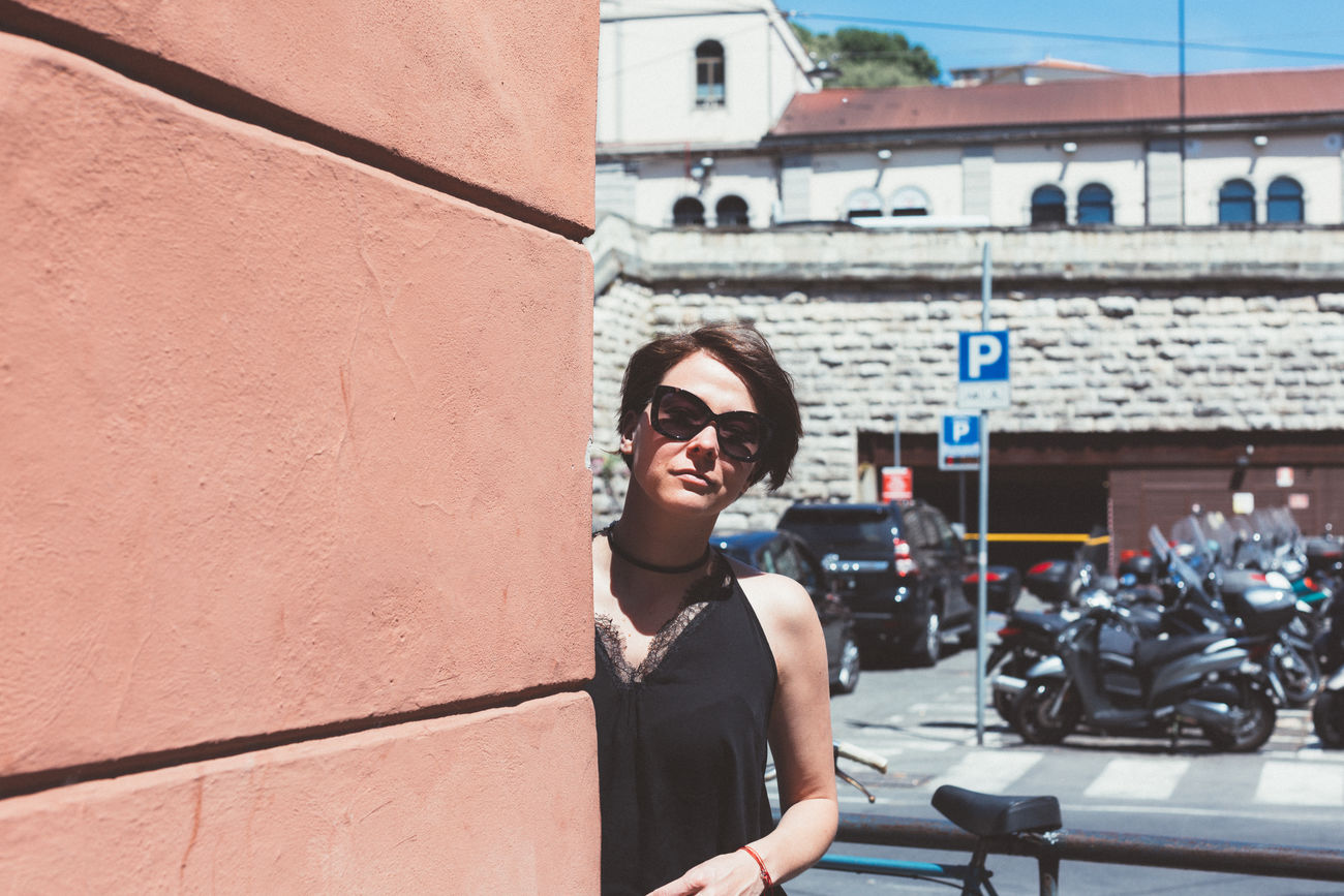 Architecture Beautiful Woman Building Exterior Built Structure Day Happiness Leisure Activity Lifestyles Looking At Camera One Person Outdoors People Portrait Real People Sky Smiling Standing Sunglasses Sunlight Travel Young Adult Young Women