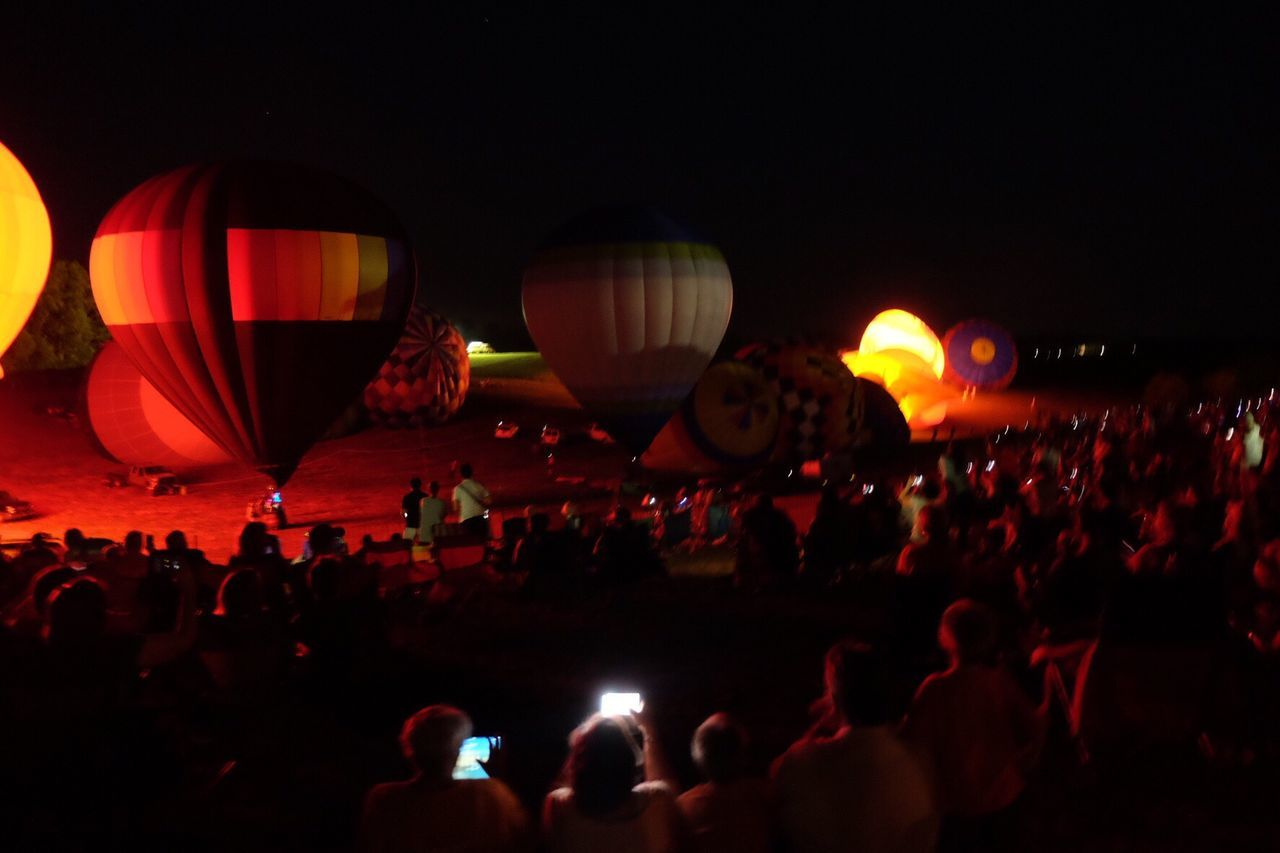 large group of people, illuminated, crowd, night, arts culture and entertainment, event, fun, leisure activity, hot air balloon, real people, ballooning festival, outdoors, people