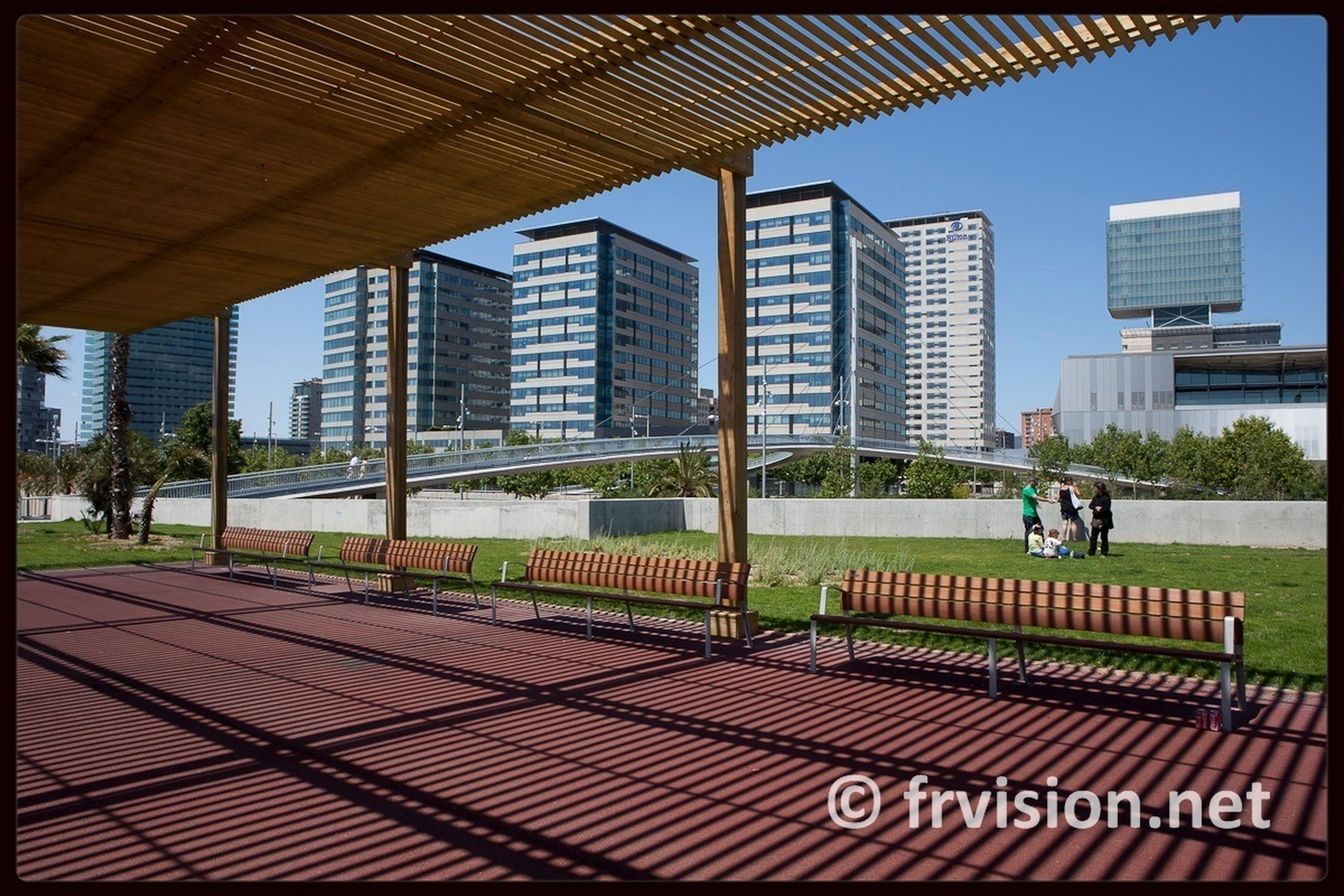 building exterior, architecture, built structure, city, transfer print, auto post production filter, grass, men, sky, city life, shadow, sunlight, office building, incidental people, tree, day, building, modern, walking