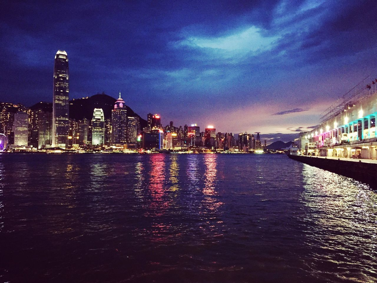 architecture, illuminated, building exterior, built structure, city, night, skyscraper, cityscape, sky, waterfront, modern, city life, water, travel destinations, urban skyline, river, cloud - sky, no people, outdoors