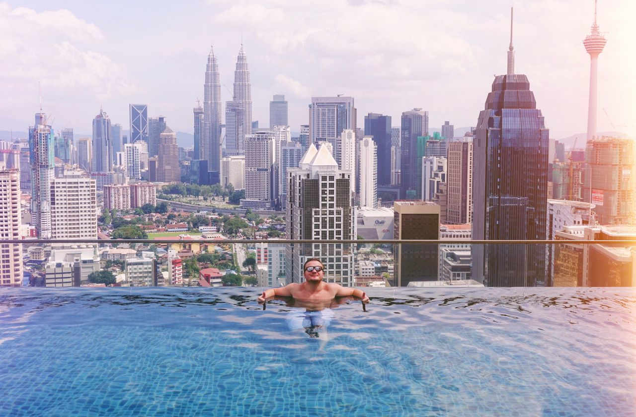 building exterior, architecture, water, skyscraper, tall - high, built structure, city, outdoors, modern, swimming pool, urban skyline, day, vacations, leisure activity, cityscape, one person, sky, travel destinations, cloud - sky, shirtless, luxury hotel, luxury, nature, one man only, mammal, people