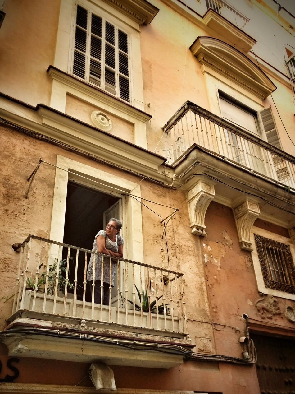 Old Woman Looking Out Of The Window on the Balcony of an Old House