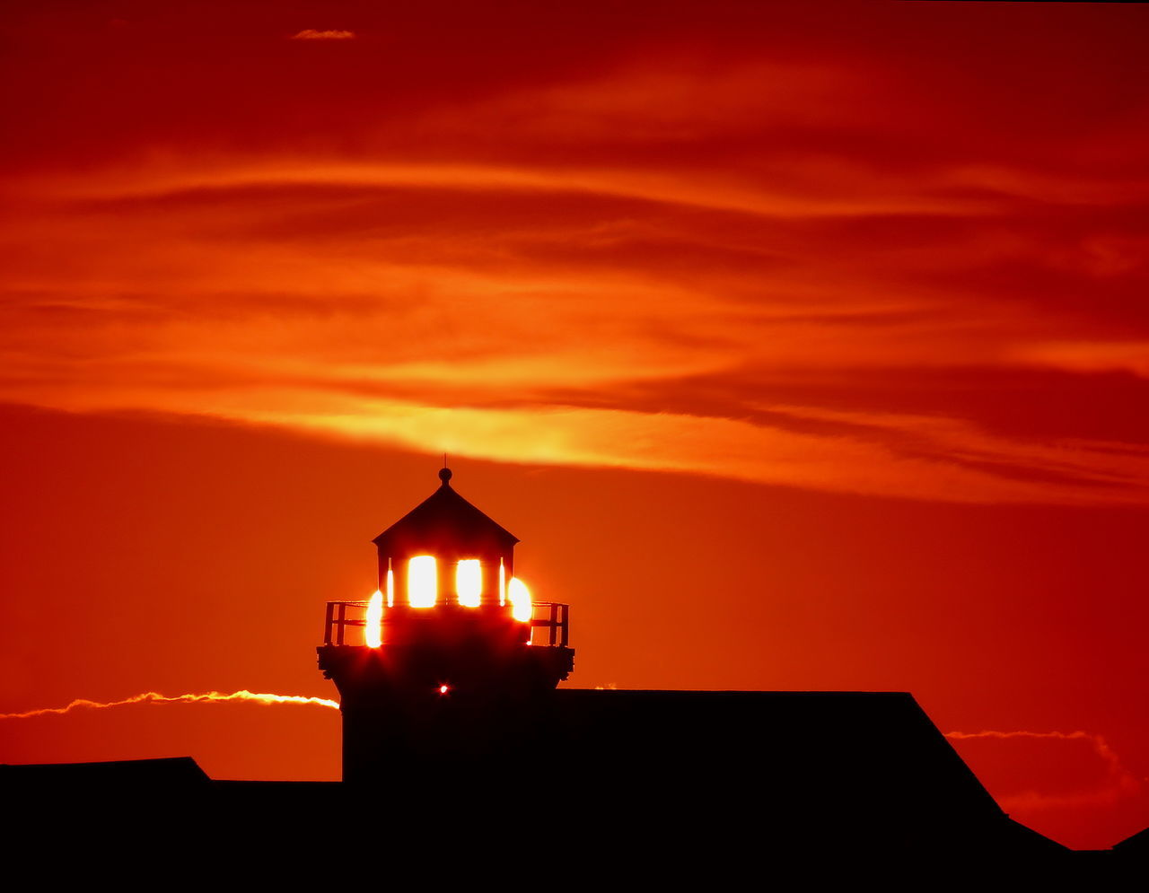 Like a guiding light of hope in the darkness, the light from the setting sun is refracted from this old lighthouse tower to send out brilliant illumination. Clouds Darkness Faith Fiery Gold Golden Guiding Help Hope Illuminated Illumination Light Lighthouse Love Orange Red Romantic Ruby Scarlet Shadow Silhouette Skies Sky Sun Sunset