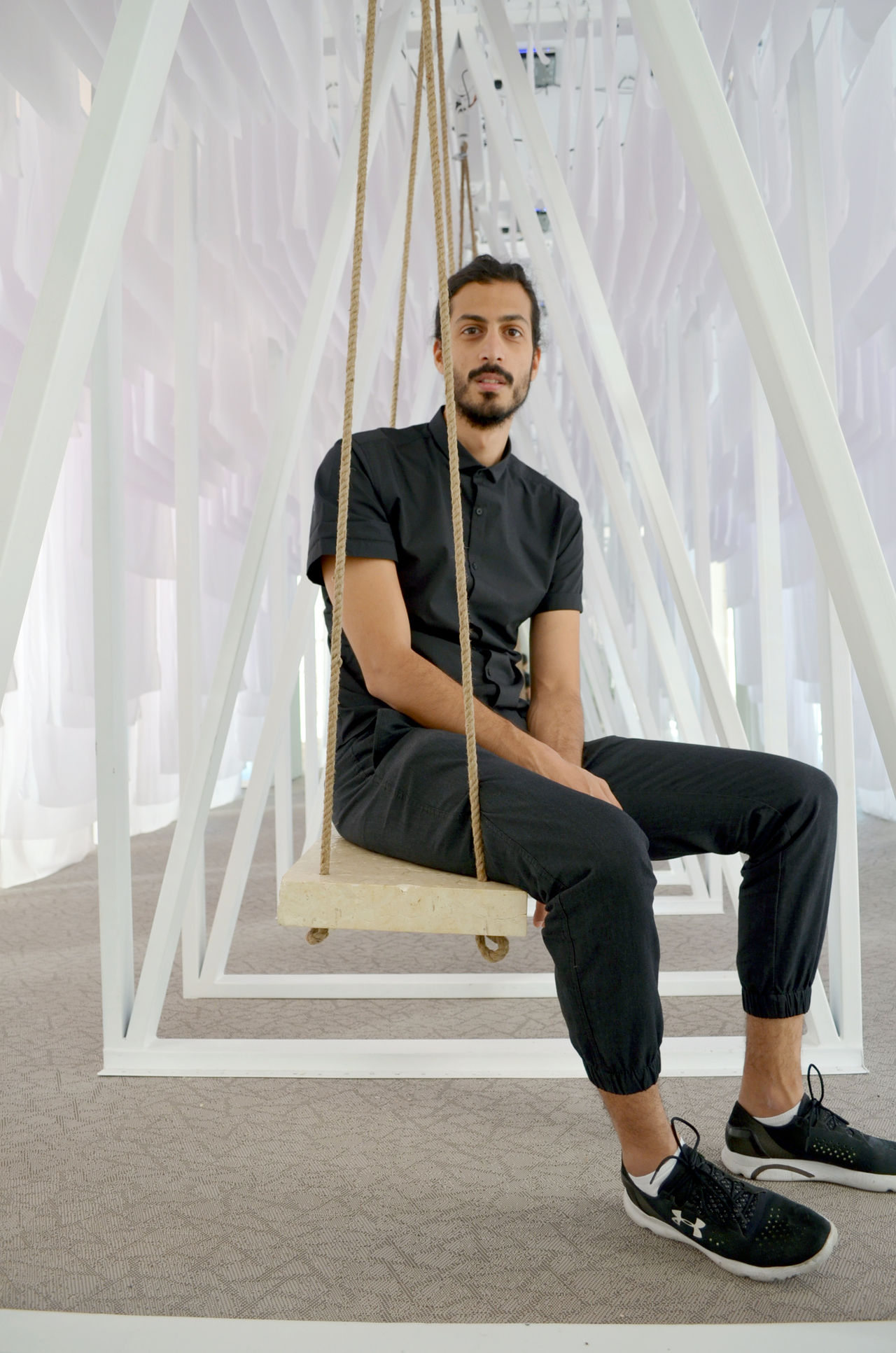 Man posing on a swing surrounded with white drapes in an art installation Adult Architecture Arcitecture Arcitecturephotography Art Installation Beard Casual Clothing Curator Curatorschoice Day Design Dubai Design Week Full Length Looking At Camera Male Model One Man Only One Person Portrait Sitting Sneakers Stone Stone Material White Drapes UnderArmour