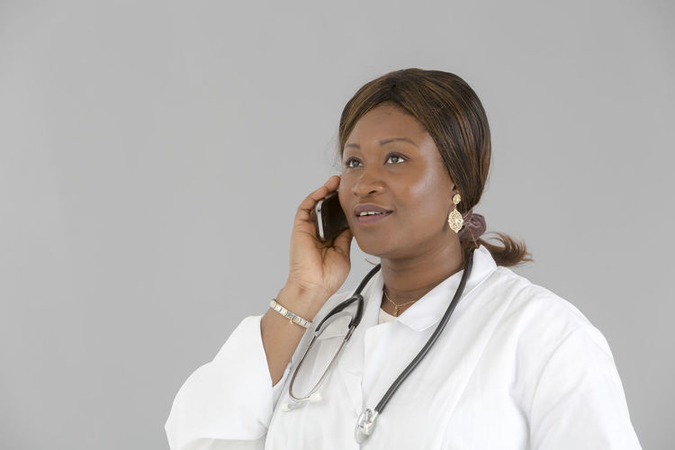 Diagnosis African Girl  Talking On The Phone Speaking On The Phone Portrait African Reassuring Beautiful Woman Reassurance Good News Occupation Clinic White Background Pediatrician Pediatrics Hospital Doctor  Nurse Medical