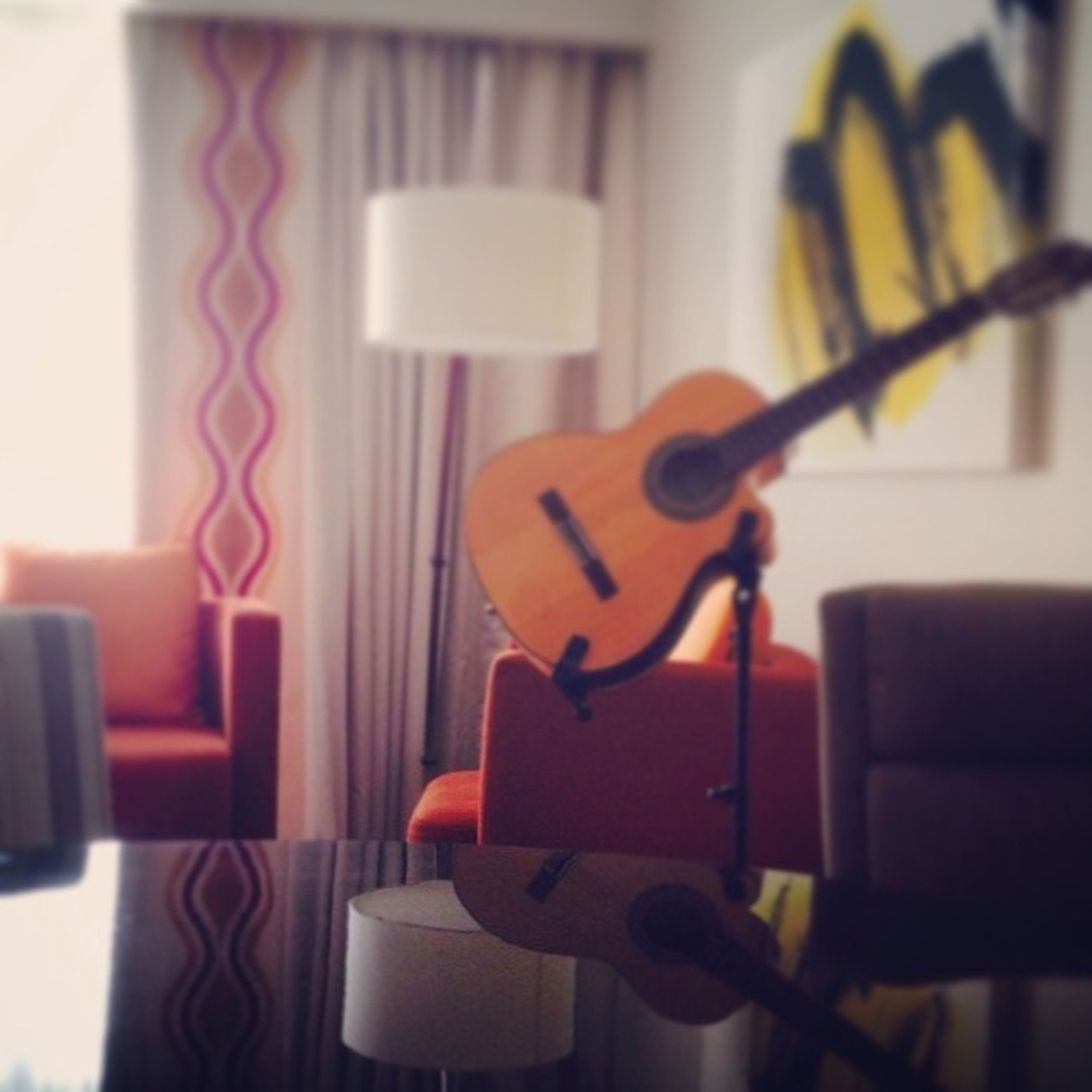 indoors, musical instrument, music, arts culture and entertainment, home interior, technology, focus on foreground, chair, musical equipment, guitar, selective focus, close-up, table, absence, communication, no people, still life, wireless technology, equipment, connection