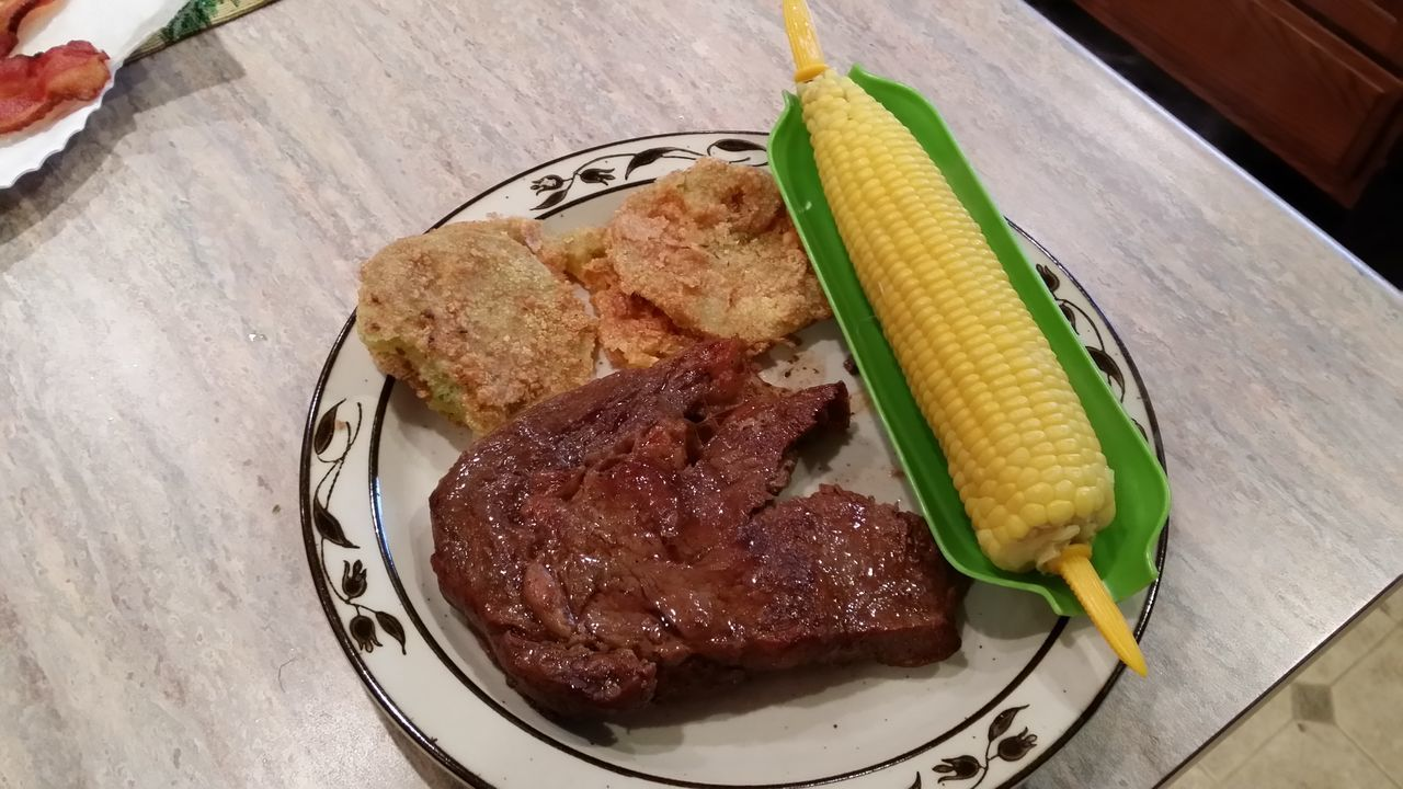 My wife take such good care of me ribeye steak corn on the cob fried green tomatoes hell yeah
