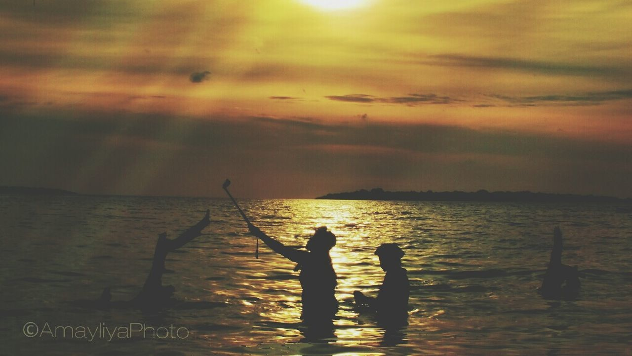 sea, water, horizon over water, sunset, silhouette, nature, scenics, real people, beauty in nature, sky, tranquil scene, standing, tranquility, outdoors, fishing, leisure activity, men, two people, togetherness, vacations, fishing pole, day, people