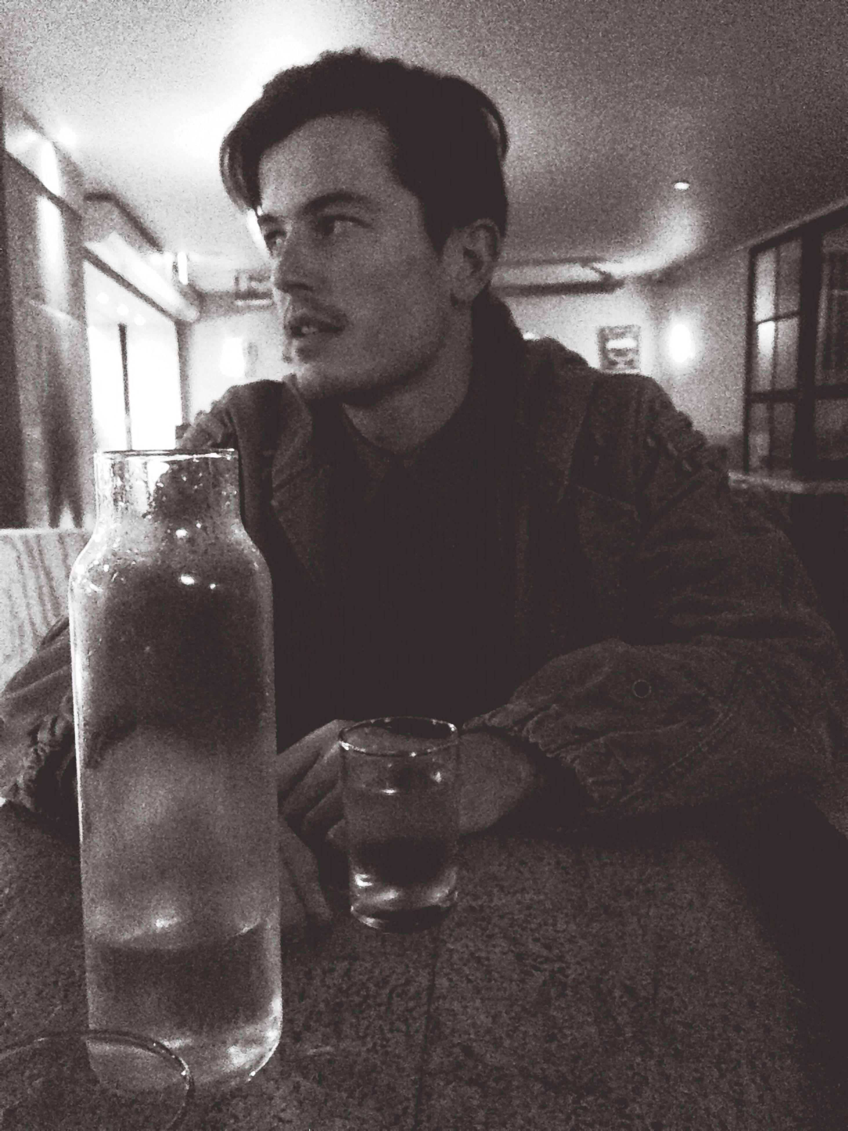 indoors, food and drink, drink, refreshment, person, lifestyles, table, leisure activity, front view, young men, looking at camera, casual clothing, holding, restaurant, freshness, home interior, drinking glass, sitting