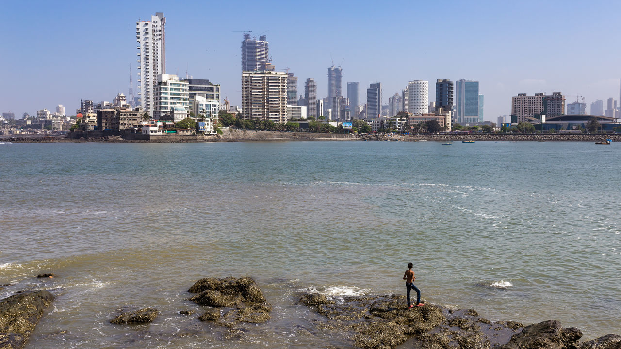 One boy standing in front of the Skyline of Mumbai, India Bombay Boy City Life Cityscape Copy Space Front India Indian Loner Man Mumbai Ocean Outdoors River Sea Skyline Small Solitude Standing Tourism Travel Travel Destinations Urban Water
