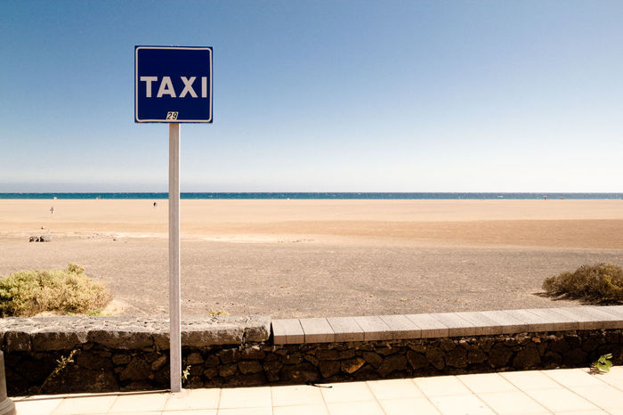 Taxi Beach Blue Clear Sky Communication Copy Space Guidance Holiday Horizon Over Water Information Sign Lanzarote Playa Del Carmen Sea Shore Sign Sky Taxi Taxi Stop Text Tourism Traffic Tranquil Scene Tranquility Water Western Script