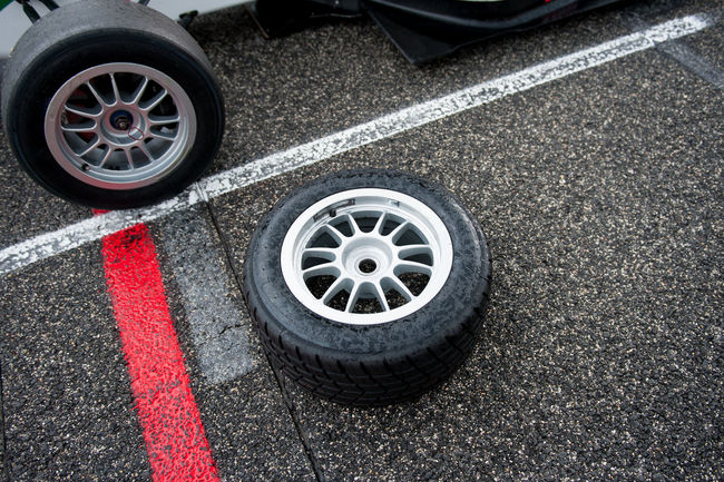 Rain tire ready for single seater car on racing starting line Asphalt Car D Day High Angle View Motor Sport Outdoors Rain Rain Tire Red Road Safety Single Seater Starting Line Tire Tired Wet Wet Race Wheel