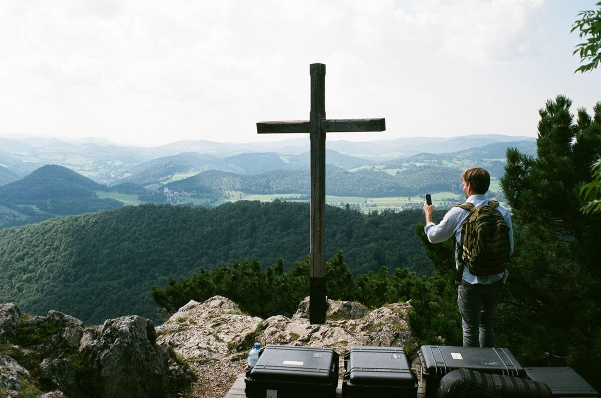 Analogue Photography Austria Beauty In Nature Cellphone Cross Forest Hiking Lonely Looking At View Mountain Mountain Peak Mountain Range Non-urban Scene Rear View Religion Scenics Sky Standing Tranquil Scene Video Production People And Places.