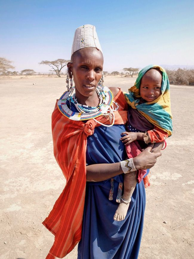 Masai Masai Tribe Masai Woman Portrait Clear Sky Portrait Looking At Camera Person Sand Casual Clothing Holding Sunlight Lifestyles Togetherness Enjoyment Riding Focus On Foreground Day People And Places Mother And Child