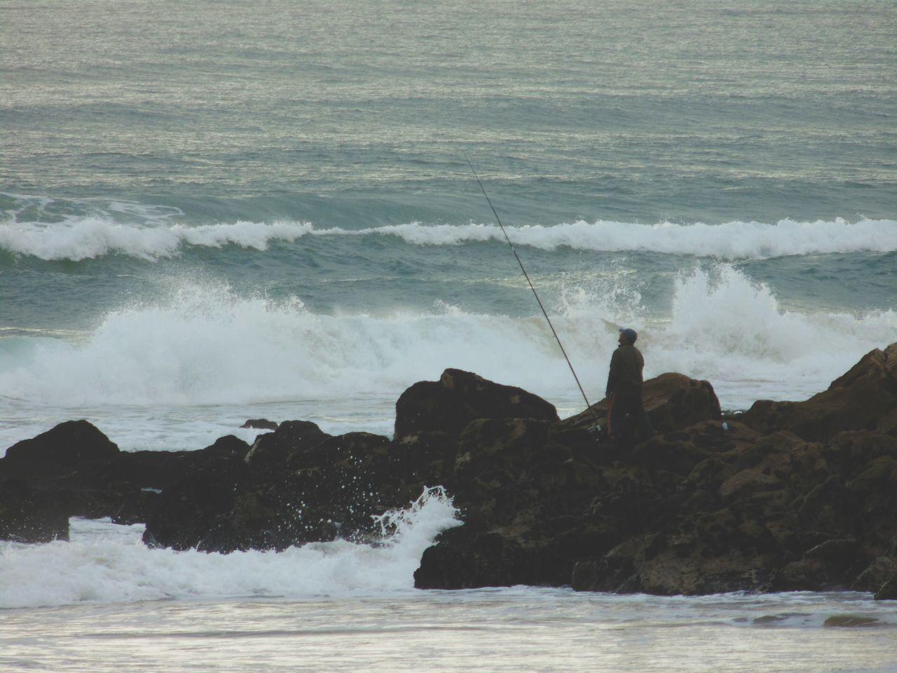 Man Fishing At Rocky Shore