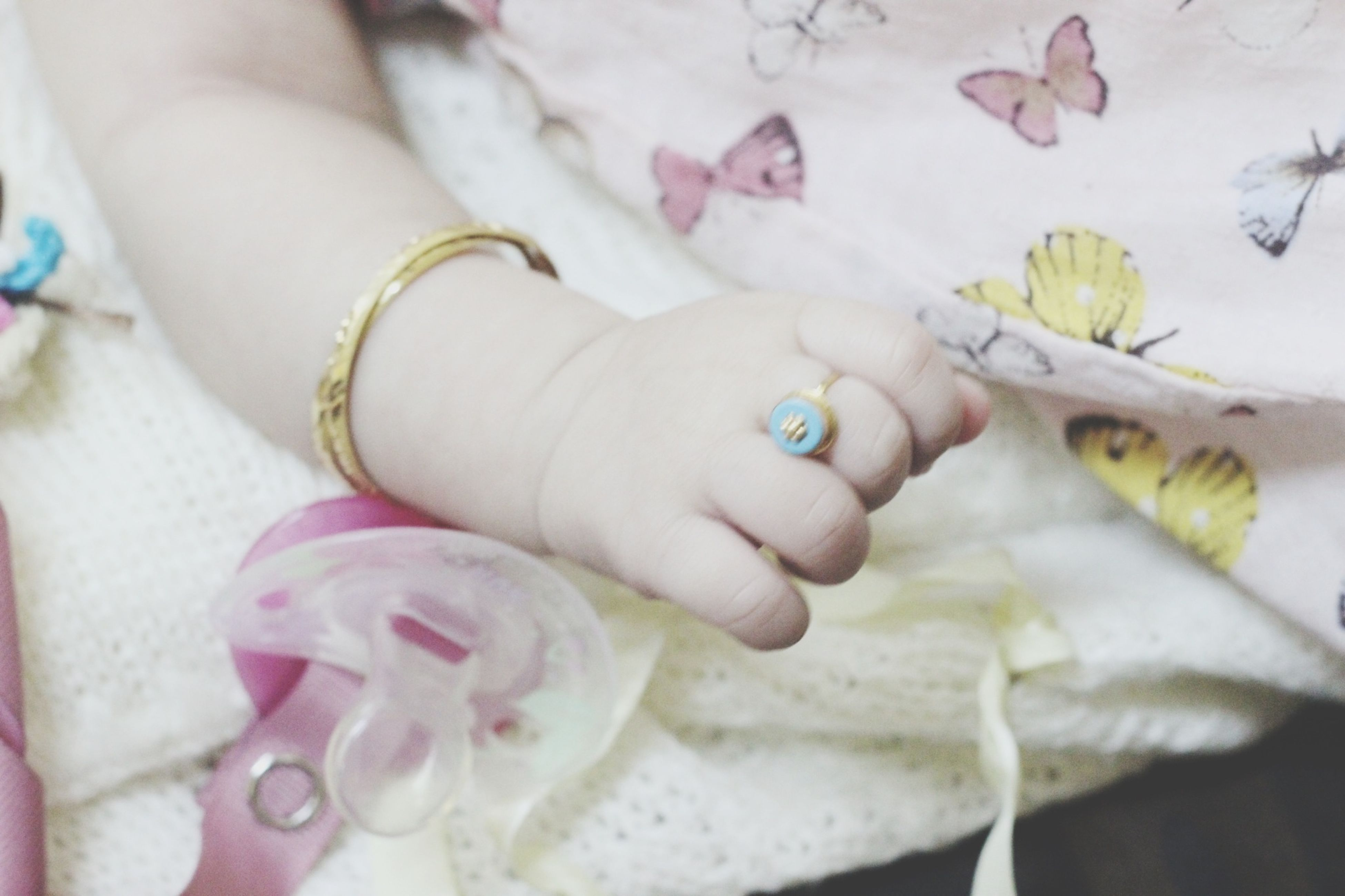 person, baby, childhood, indoors, unknown gender, lifestyles, fragility, babyhood, flower, holding, innocence, part of, close-up, leisure activity, petal
