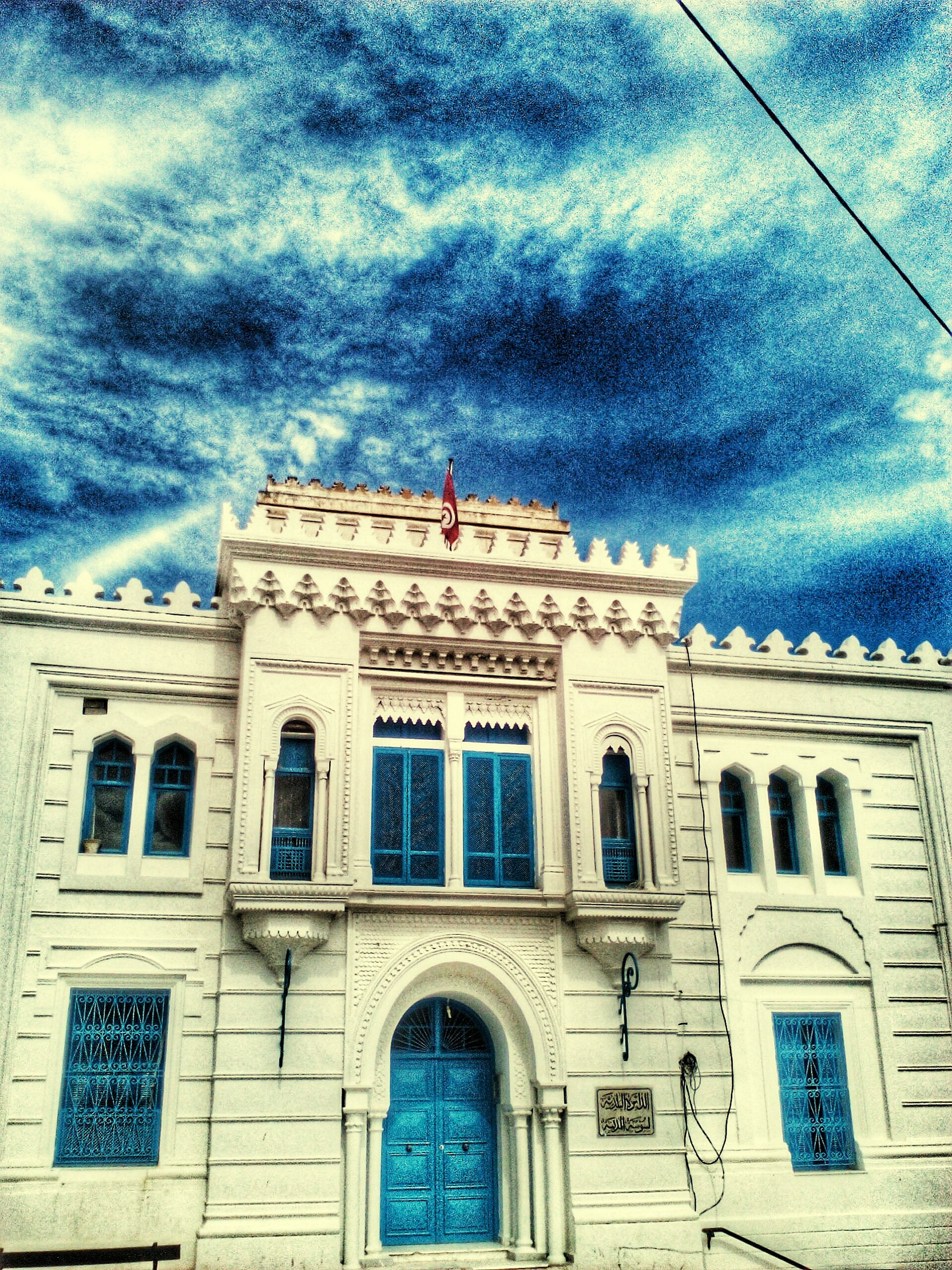 architecture, building exterior, built structure, sky, low angle view, cloud - sky, arch, window, cloudy, cloud, facade, church, blue, building, outdoors, day, religion, history, no people, old