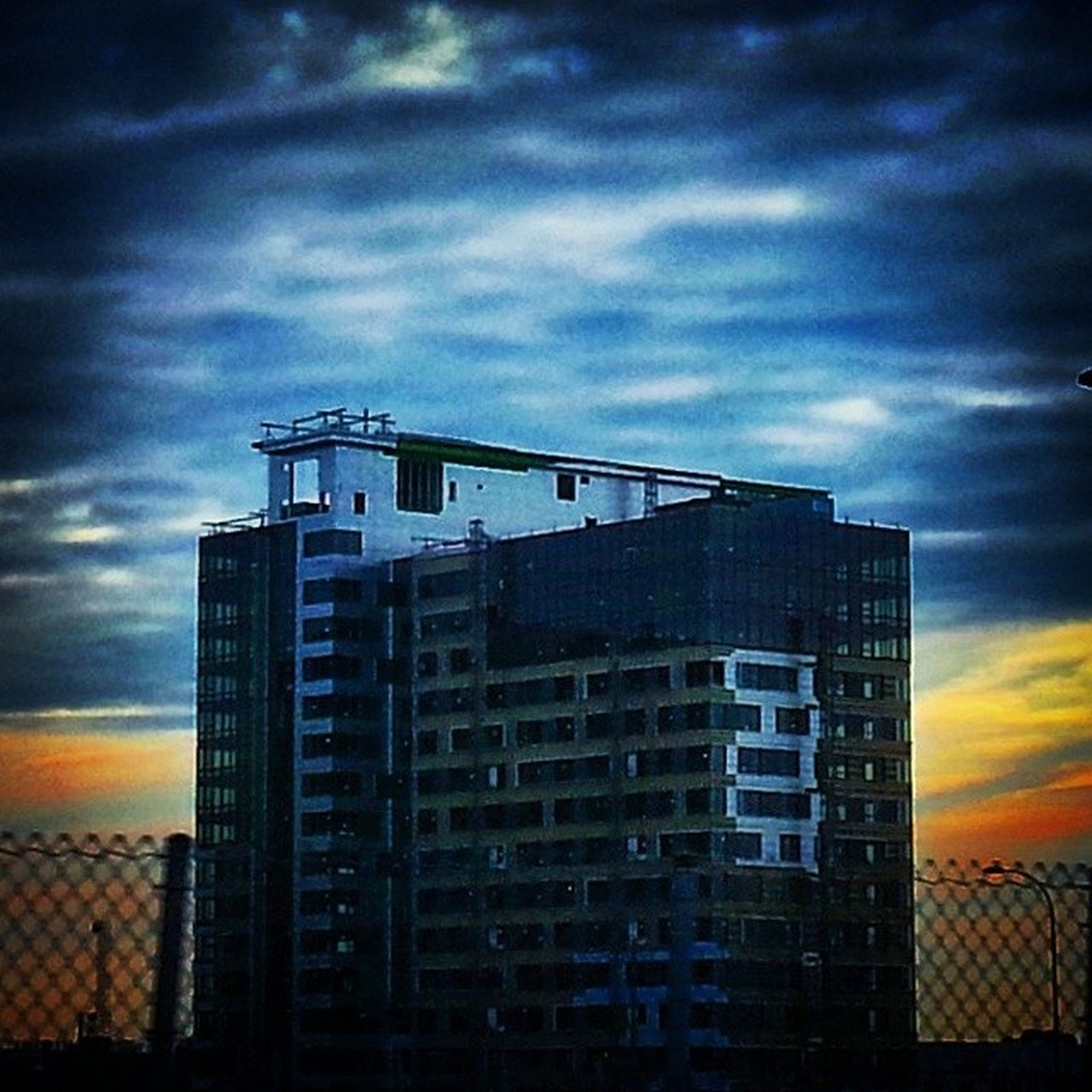 architecture, building exterior, built structure, sky, cloud - sky, sunset, cloudy, low angle view, cloud, city, building, window, modern, orange color, residential building, residential structure, weather, dramatic sky, outdoors, no people