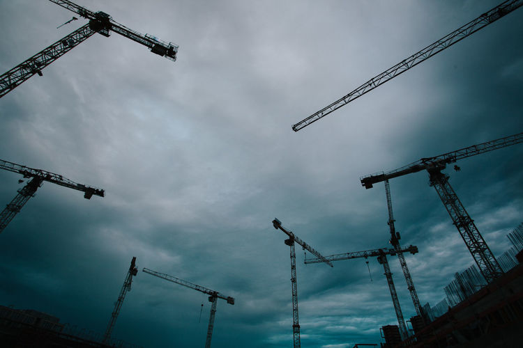 Busy Dark Economy Storm Cloud - Sky Construction Construction Site Crane Crane - Construction Machinery Day Depression Low Angle View Negativity No People Outdoors Sky