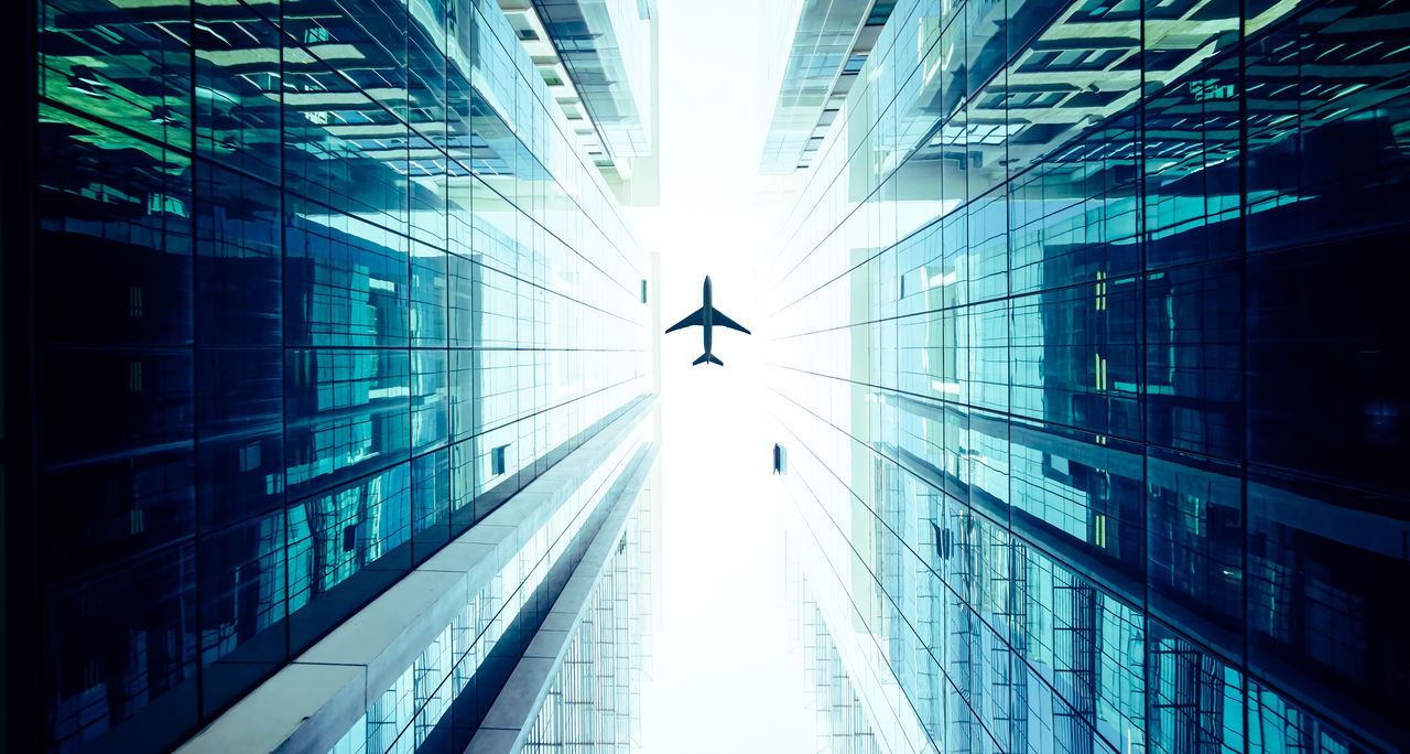 airplane flying above glass office buildings. Architecture Building Exterior Built Structure Business Business Finance And Industry City City Life Day Downtown District Futuristic Illuminated Modern No People Office Building Exterior Outdoors Reflection Sky Skyscraper Technology Tunnel