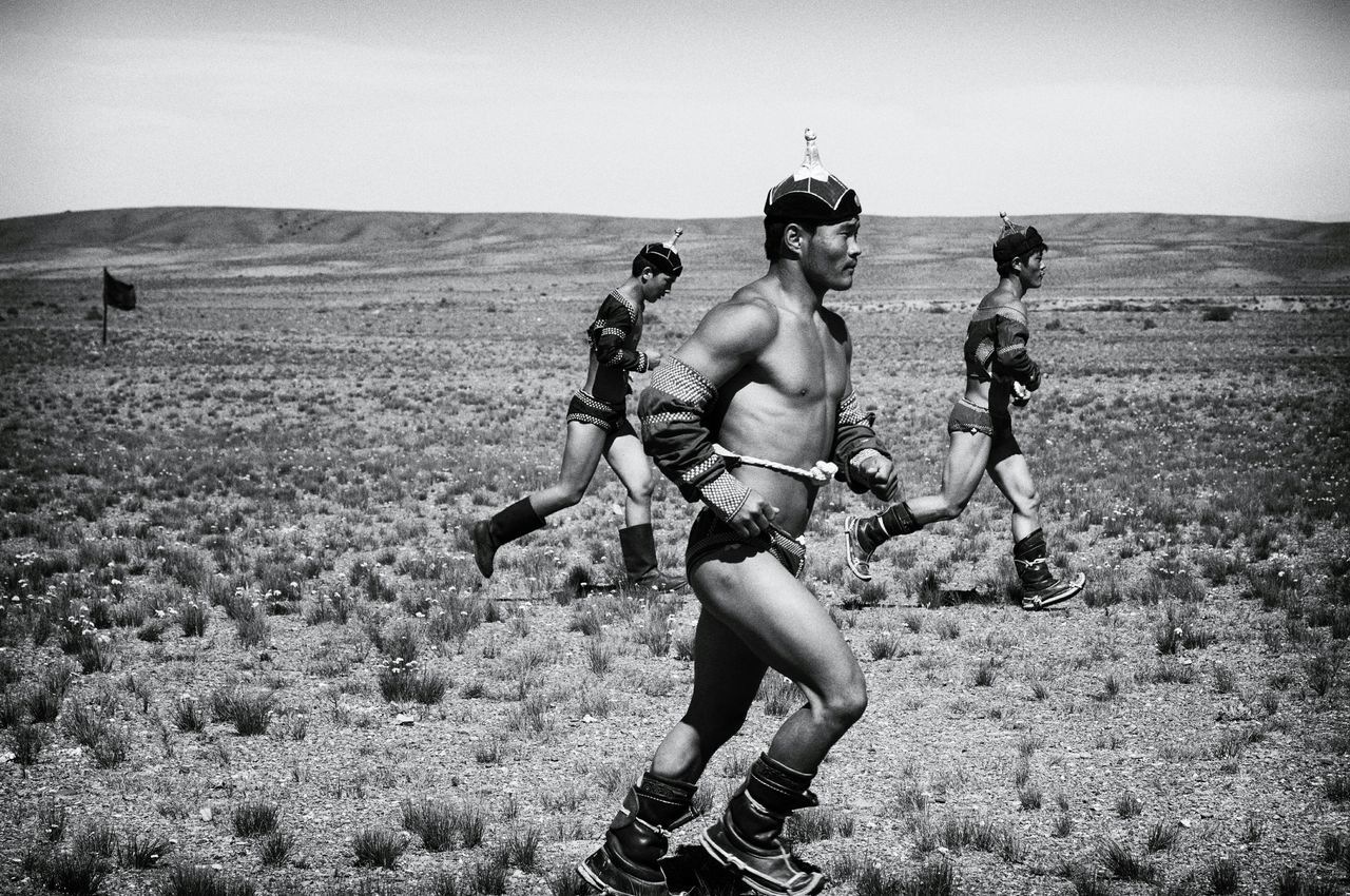 """Untold Stories Naadam Mongolia Traditional Mongolian Wrestling Lotta Tradizionale Mongola Reportage Documentary Photography Black And White Bianco E Nero Claudia Ioan TRADITIONAL MONGOLIAN WRESTLING Wrestling is the most important of the Mongolian culture's historic """"Three Manly Skills"""" played in the Nadaam (""""Game"""") every year, that also include horsemanship and archery. Naadams always attract huge crowds of participants and public. Nowadays, when a male child is born in a family,Mongols wish him to become a wrestler. Telling Stories Differently EyeEm x ICP - Telling Stories Differently People And Places"""