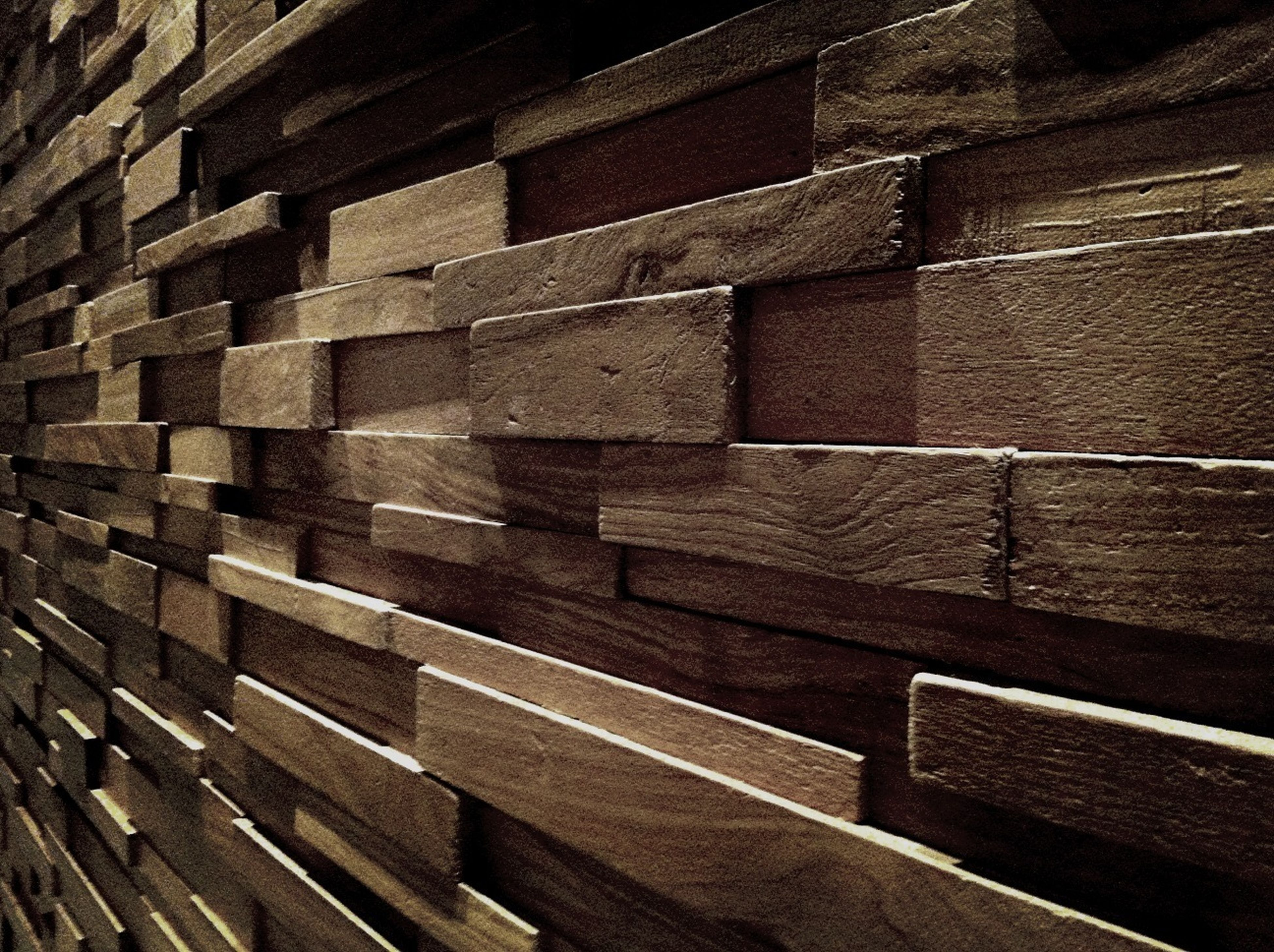 wood - material, backgrounds, full frame, textured, pattern, large group of objects, wooden, high angle view, in a row, abundance, stack, wood, repetition, no people, outdoors, day, wall - building feature, sunlight, close-up, brick wall