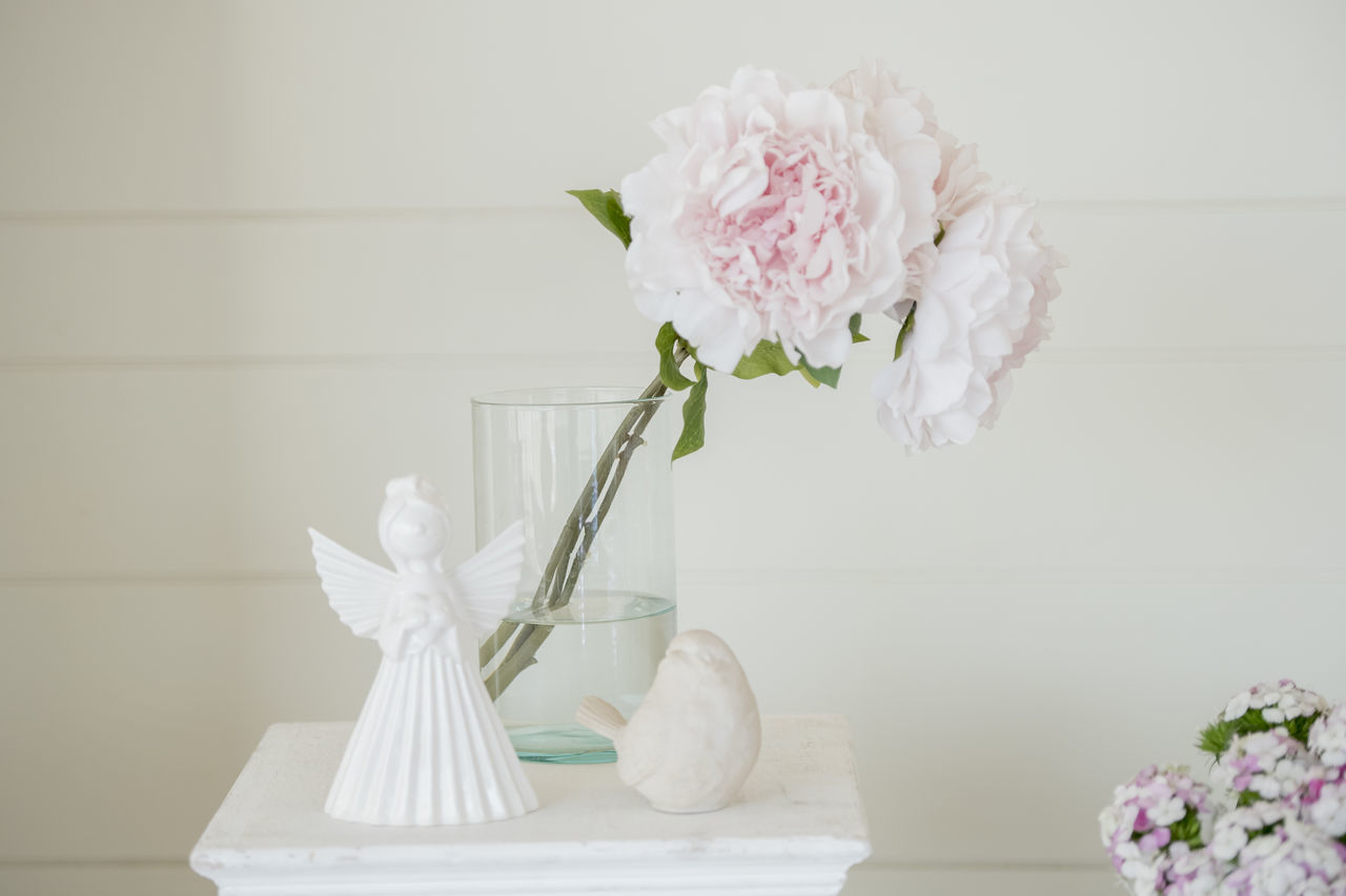 Close-Up Of Flower Vase By Statues On Side Table Against Wall At Wedding