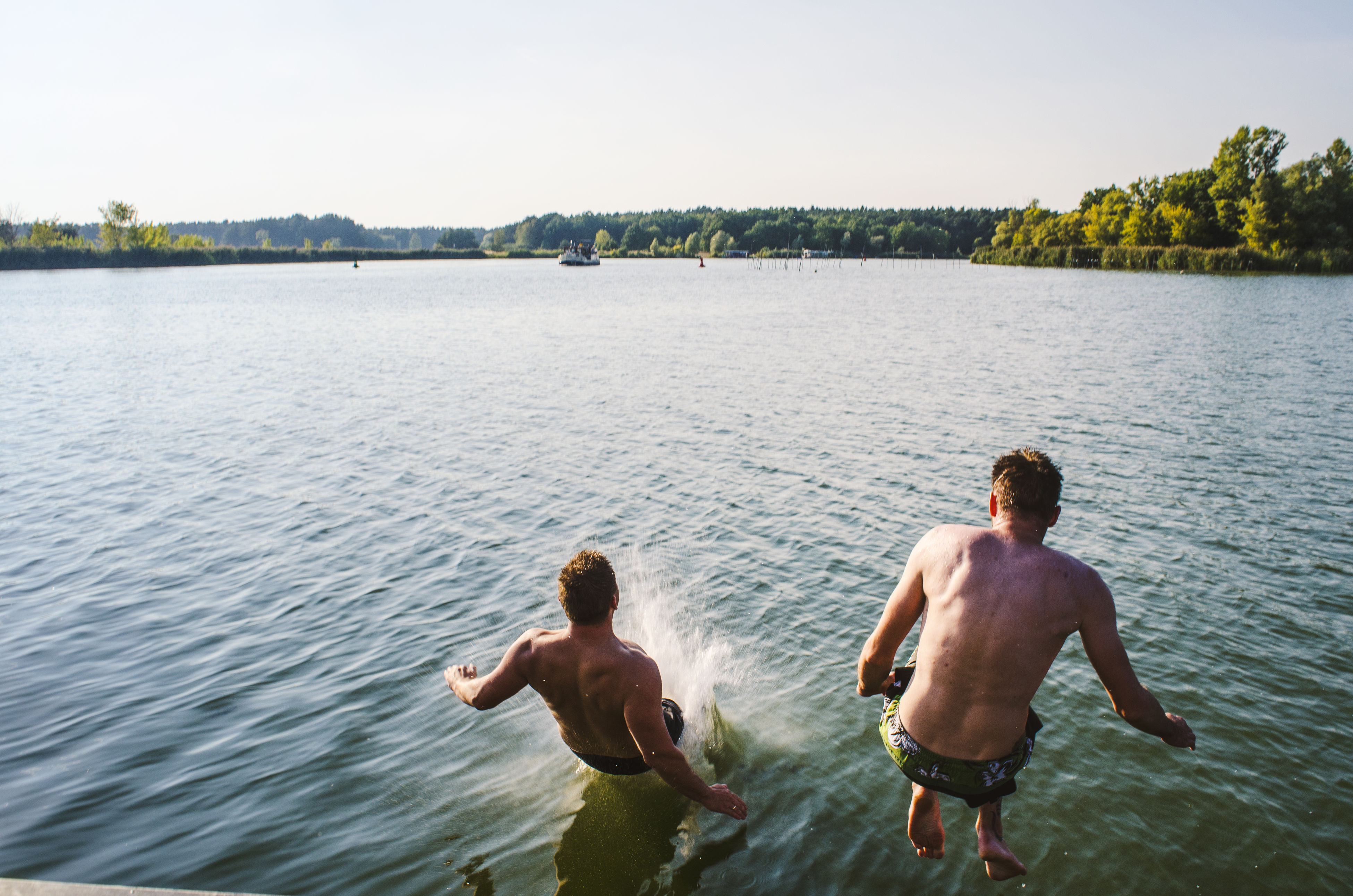 water, rear view, leisure activity, outdoors, togetherness, day, real people, men, two people, lake, vacations, swimming, shirtless, nature, young adult, sky, adult, people