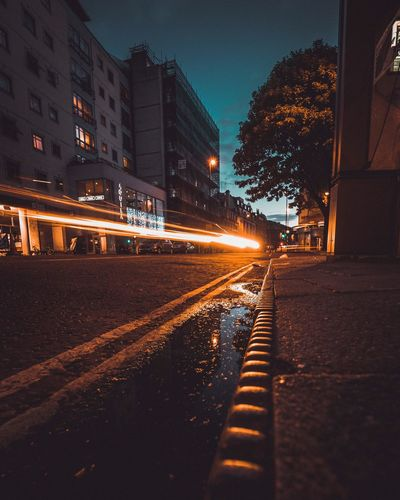 Illuminated Night Street Building Exterior Transportation Architecture Built Structure Speed Road City No People Light Trail Outdoors Long Exposure Street Light Motion Sky High Street Tree Land Vehicle