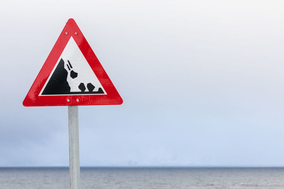 Falling rocks road warning sign Cliff Communication Danger Copy Space Falling Forecasting Guidance Lofoten And Vesteral Islands No People Outdoors Overcast Road Sign Road Warning Sign Rock - Object Safety Sea Sign Single Object Sky Symbol Triangle Shape Warning Sign Water Weather Winter