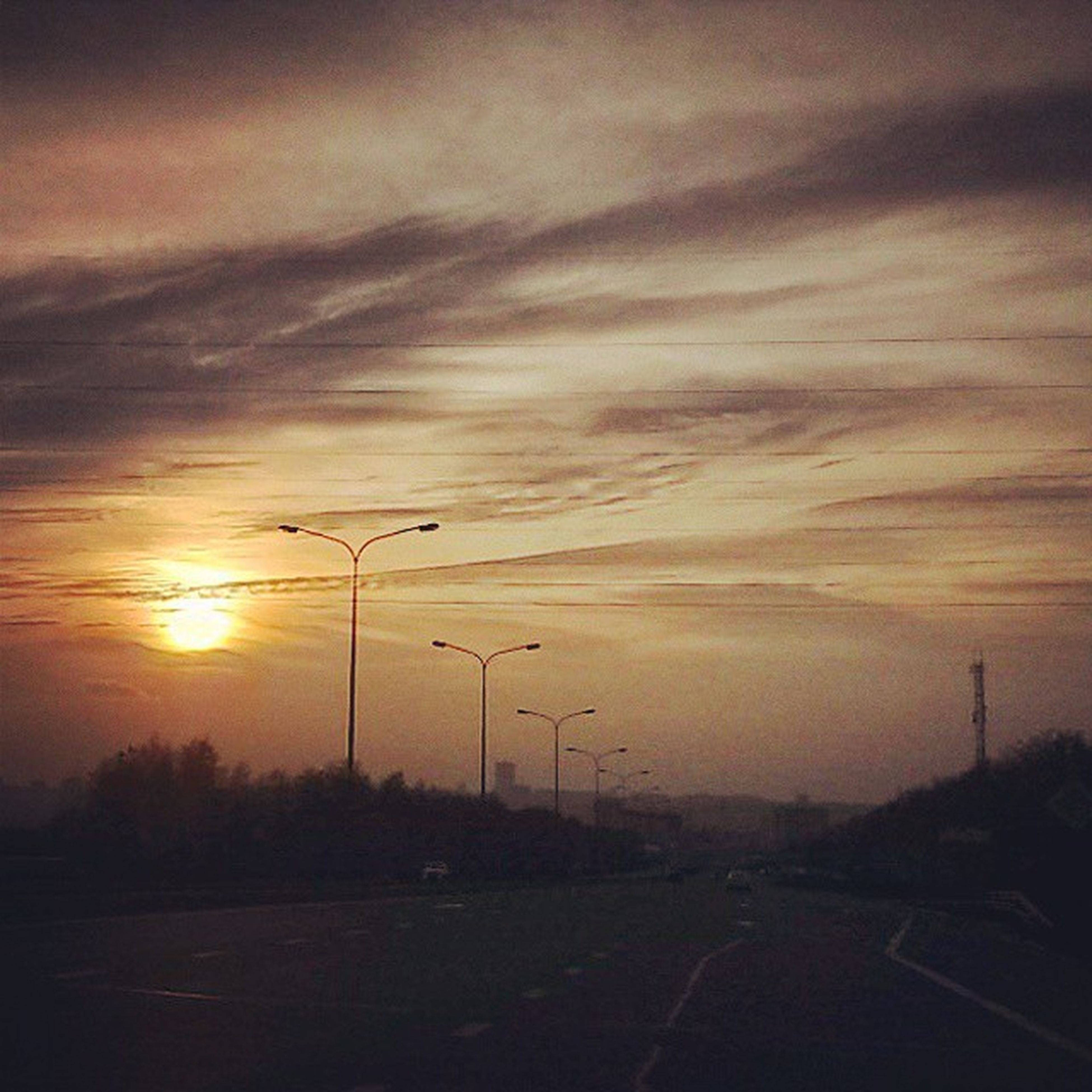 sunset, sky, road, tranquility, electricity pylon, landscape, tranquil scene, scenics, the way forward, silhouette, cloud - sky, beauty in nature, nature, orange color, street light, transportation, power line, electricity, idyllic, cloudy