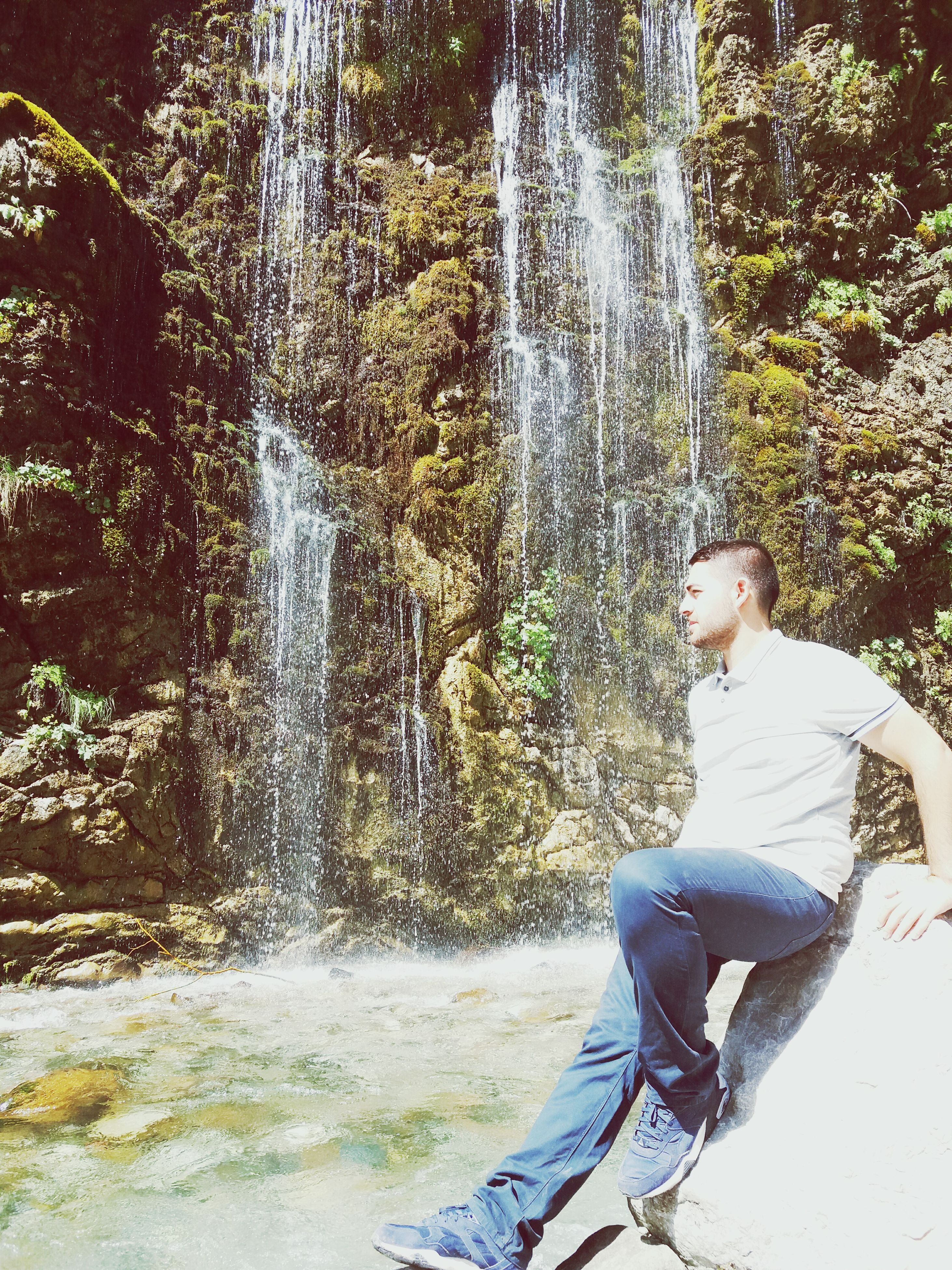 side view, motion, relaxation, sitting, full length, young adult, spraying, casual clothing, waterfall, day, summer, outdoors, person, enjoyment, park, nature, tranquil scene, contemplation, tranquility, non-urban scene