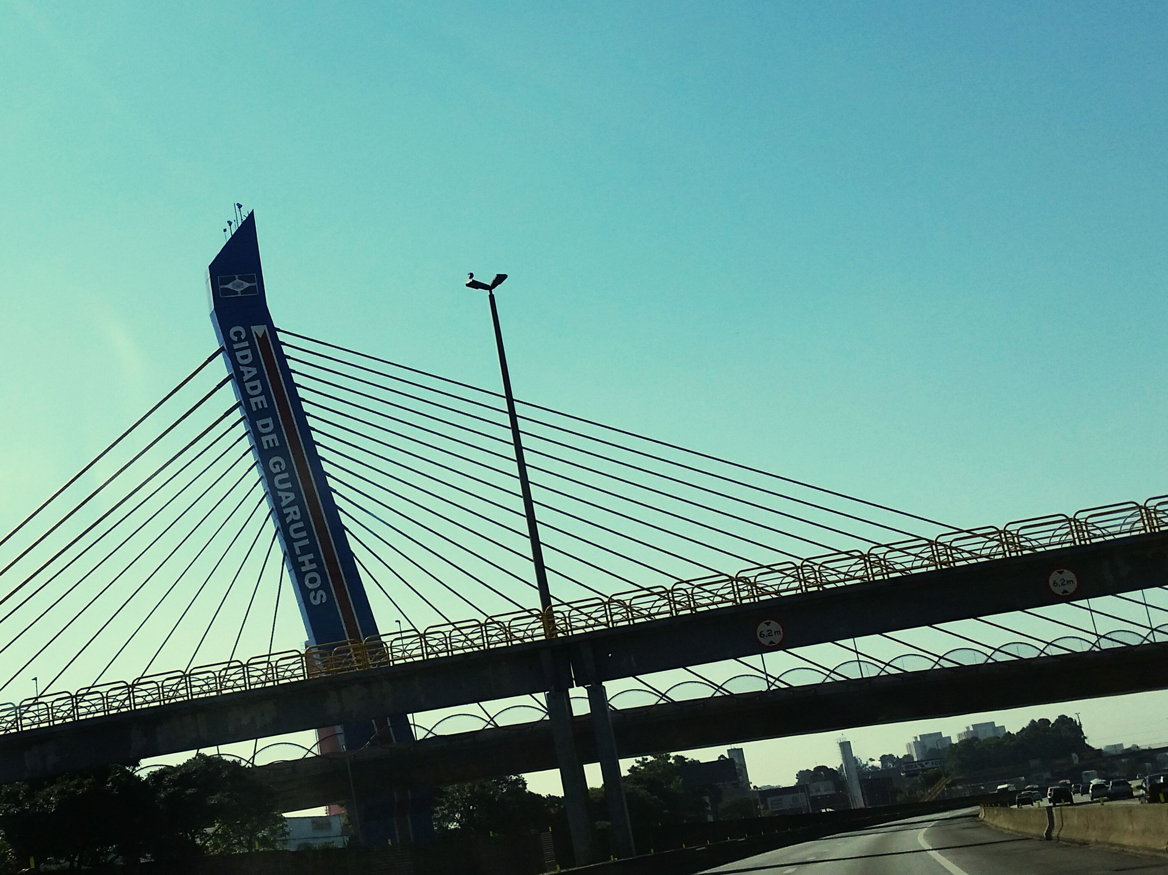 clear sky, built structure, architecture, low angle view, copy space, connection, bridge - man made structure, city, engineering, building exterior, blue, bridge, transportation, suspension bridge, outdoors, modern, silhouette, sky, day, metal