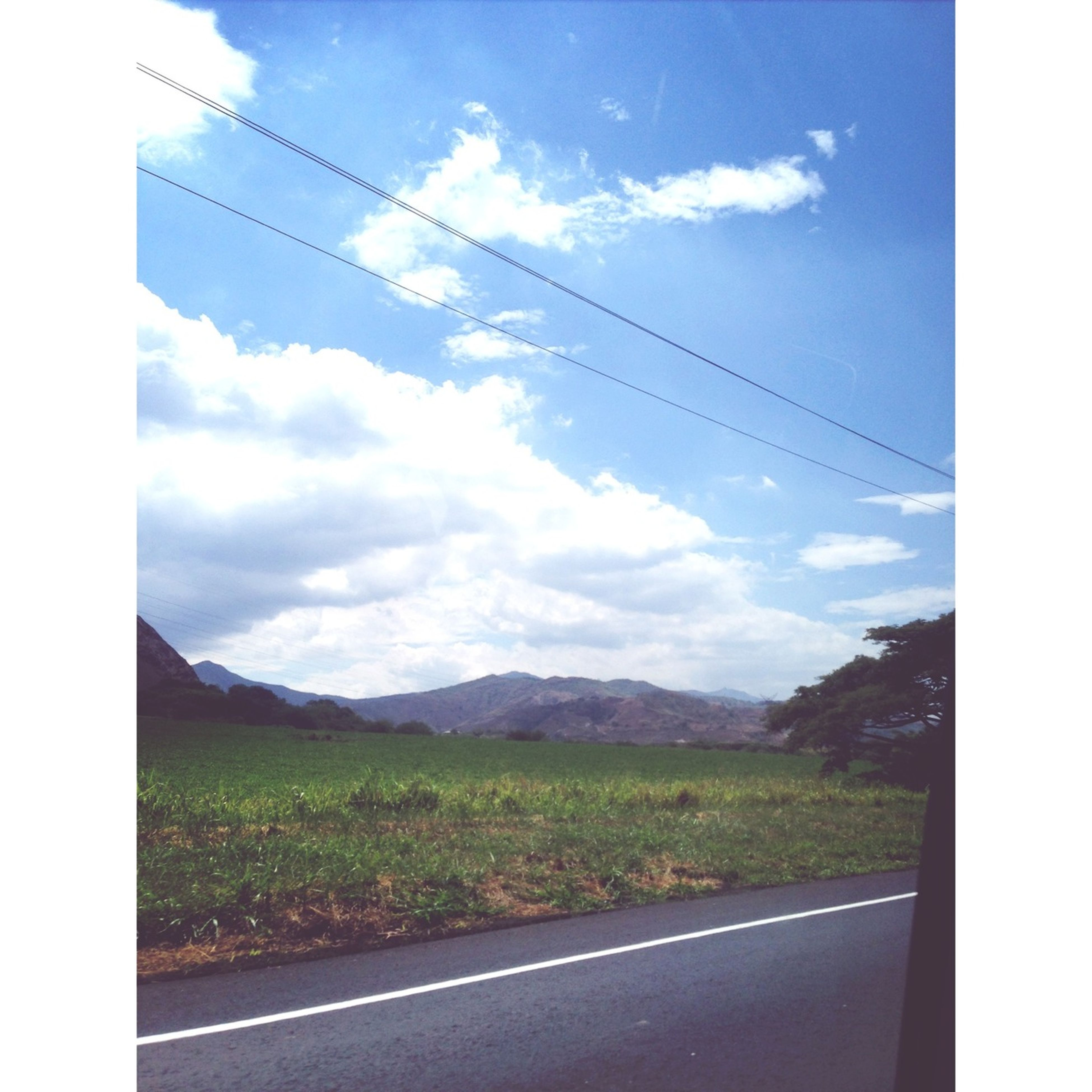 sky, mountain, transportation, transfer print, power line, road, electricity pylon, landscape, tranquil scene, scenics, tranquility, cloud - sky, mountain range, cloud, country road, nature, beauty in nature, power supply, cable, auto post production filter