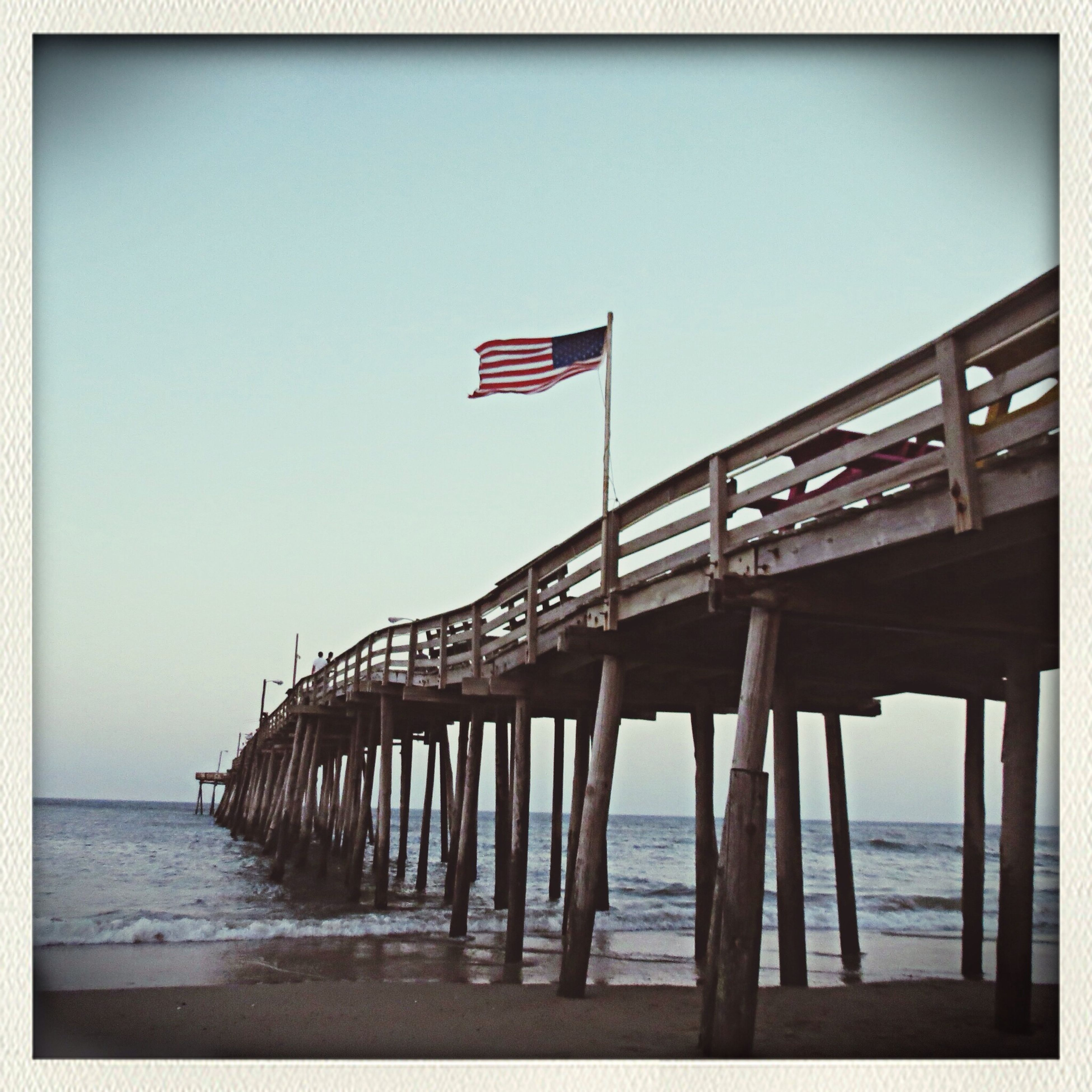sea, water, beach, horizon over water, clear sky, built structure, copy space, flag, transfer print, shore, tranquility, architecture, sky, tranquil scene, pier, auto post production filter, sand, nature, blue, day