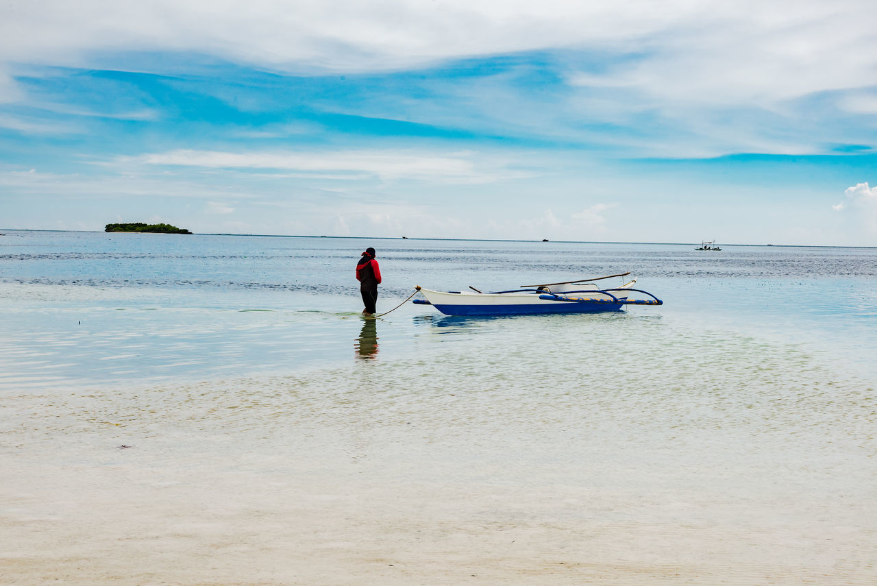 sea, sky, water, cloud - sky, nature, real people, beach, men, day, beauty in nature, scenics, nautical vessel, horizon over water, one person, outdoors, transportation, standing, full length, occupation, outrigger, people
