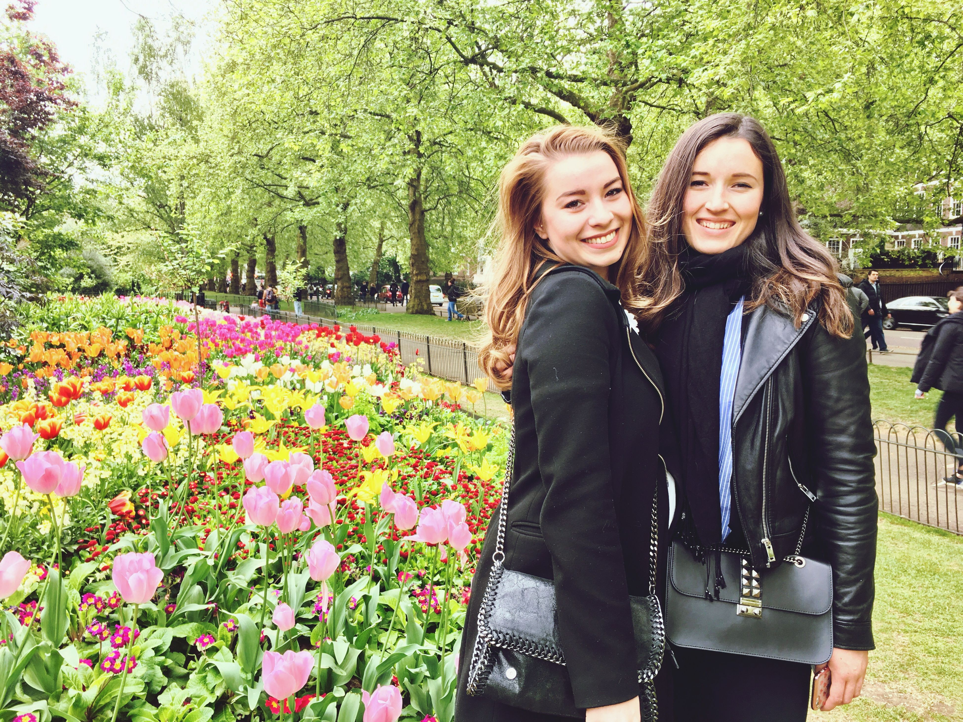 flower, two people, real people, smiling, young women, young adult, day, happiness, togetherness, outdoors, leisure activity, nature, growth, beautiful woman, lifestyles, beauty in nature, women, tree, friendship, people
