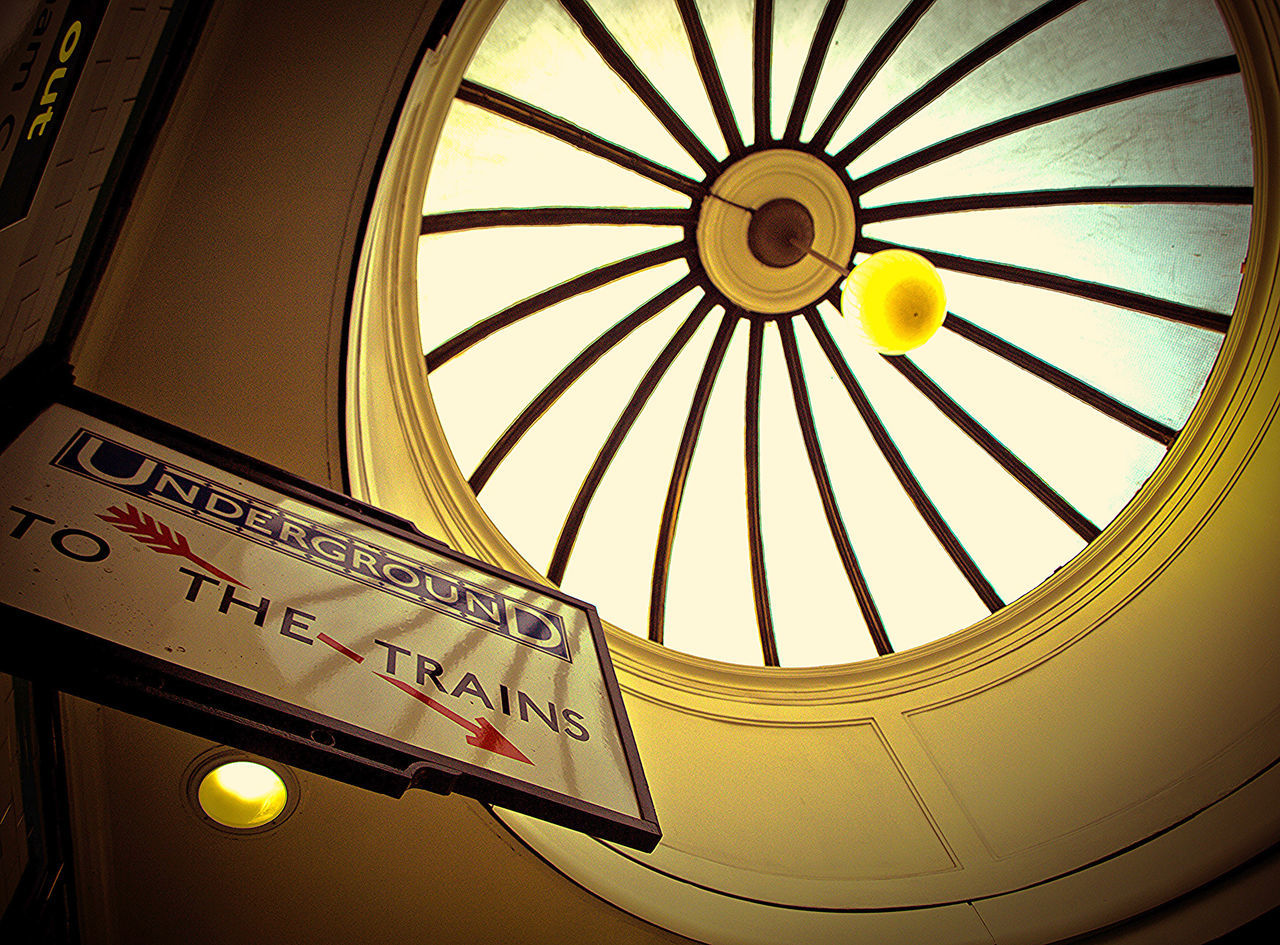 Low Angle View Of Directional Sign Against Cupola At Railroad Station