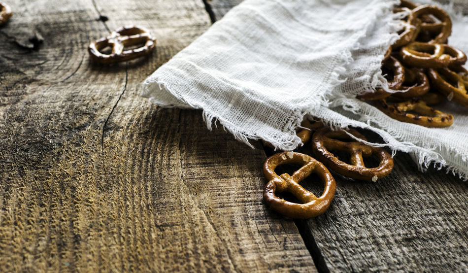 Heap of fresh Wheat salt pretzels on hessian linen fabric cloth and wooden table Cloth Fabric Fresh Freshness Heap Hessian Linen Man Made Object Pretzels Salt Table Wheat Wooden Fresh On Market 2016