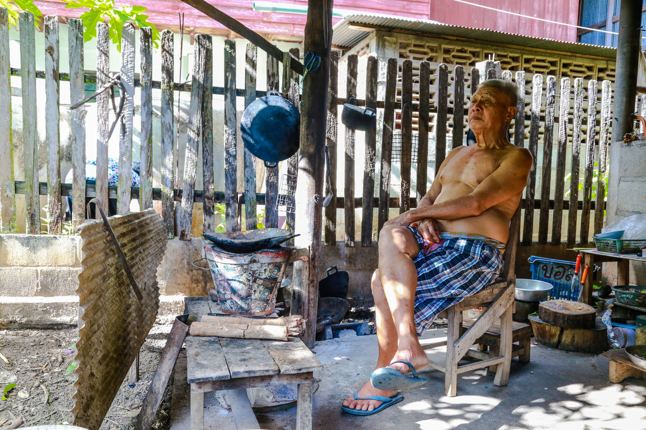 Old men are sitting at home cooking in Ban Hong is a district of Lamphun Province, northern Thailand. Cooking At Home Wait Adult Adults Only Day Elderly Man Full Length Lifestyles Men Old People, Man One Man Only One Person Only Men Outdoors People Real People Shirtless Sitting Young Adult