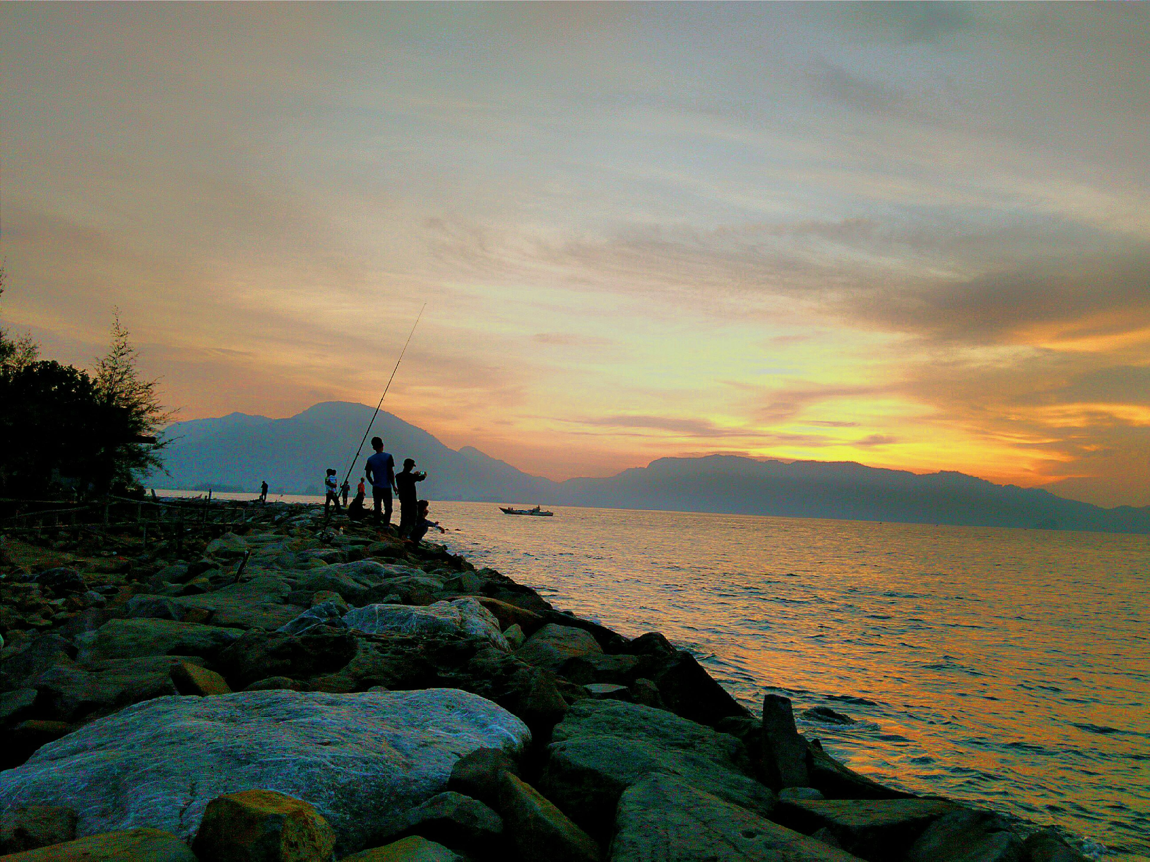 water, sunset, scenics, sea, sky, beauty in nature, tranquility, tranquil scene, silhouette, nature, rock - object, idyllic, orange color, cloud - sky, men, leisure activity, lifestyles, horizon over water, transportation