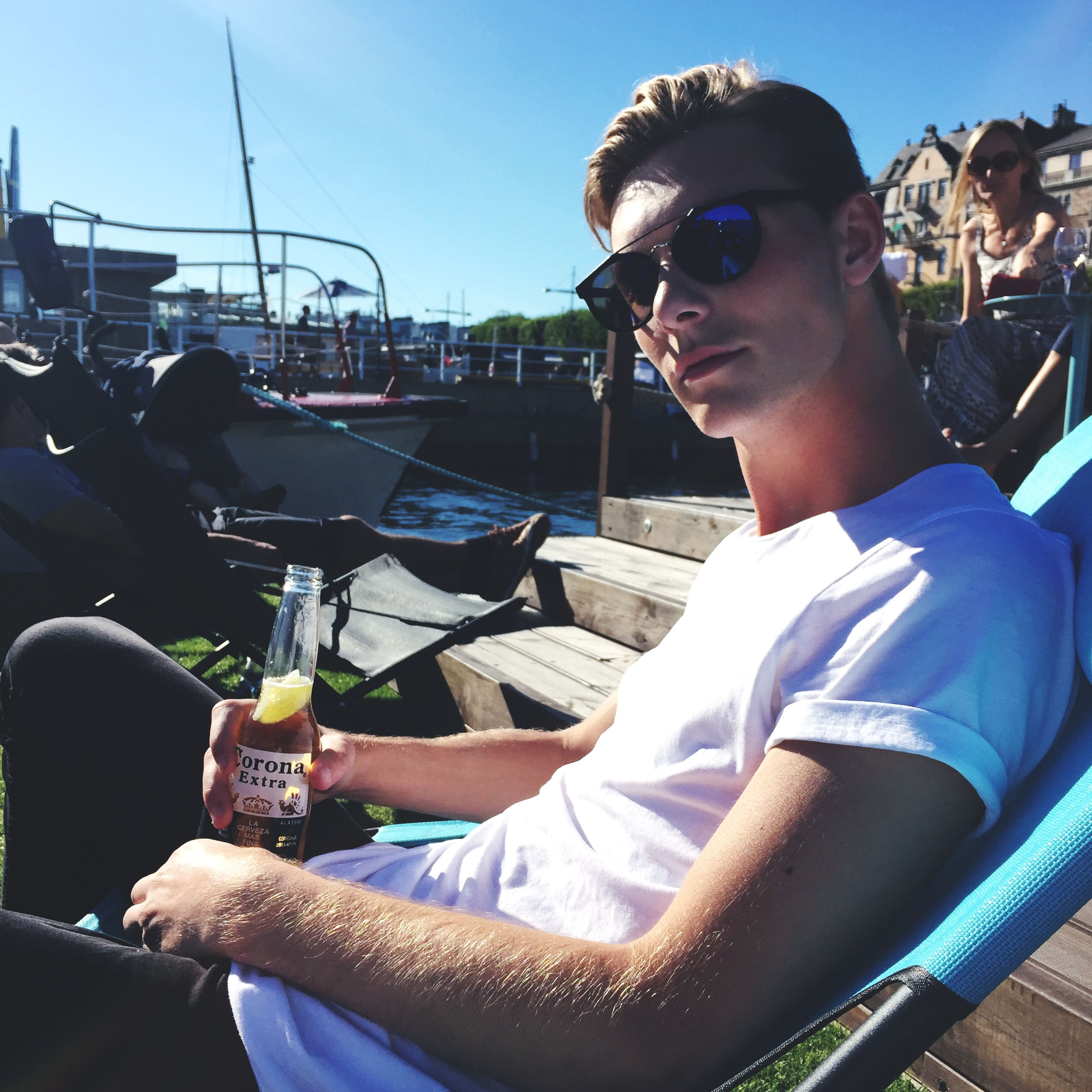 person, young adult, casual clothing, lifestyles, front view, leisure activity, sunglasses, young men, sitting, portrait, looking at camera, smiling, transportation, holding, waist up, three quarter length, happiness