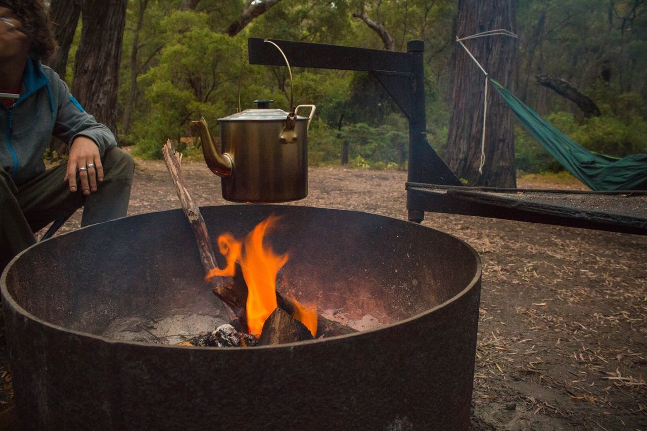 real people, camping, burning, outdoors, one person, flame, heat - temperature, day, tree, fire pit, lifestyles, bonfire, nature, camping stove, human hand, people