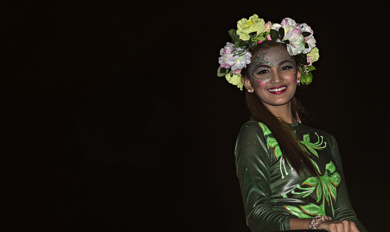 one person, young adult, flower, studio shot, copy space, front view, happiness, real people, looking at camera, smiling, portrait, leisure activity, laurel wreath, standing, black background, lifestyles, young women, outdoors, day, adult, people