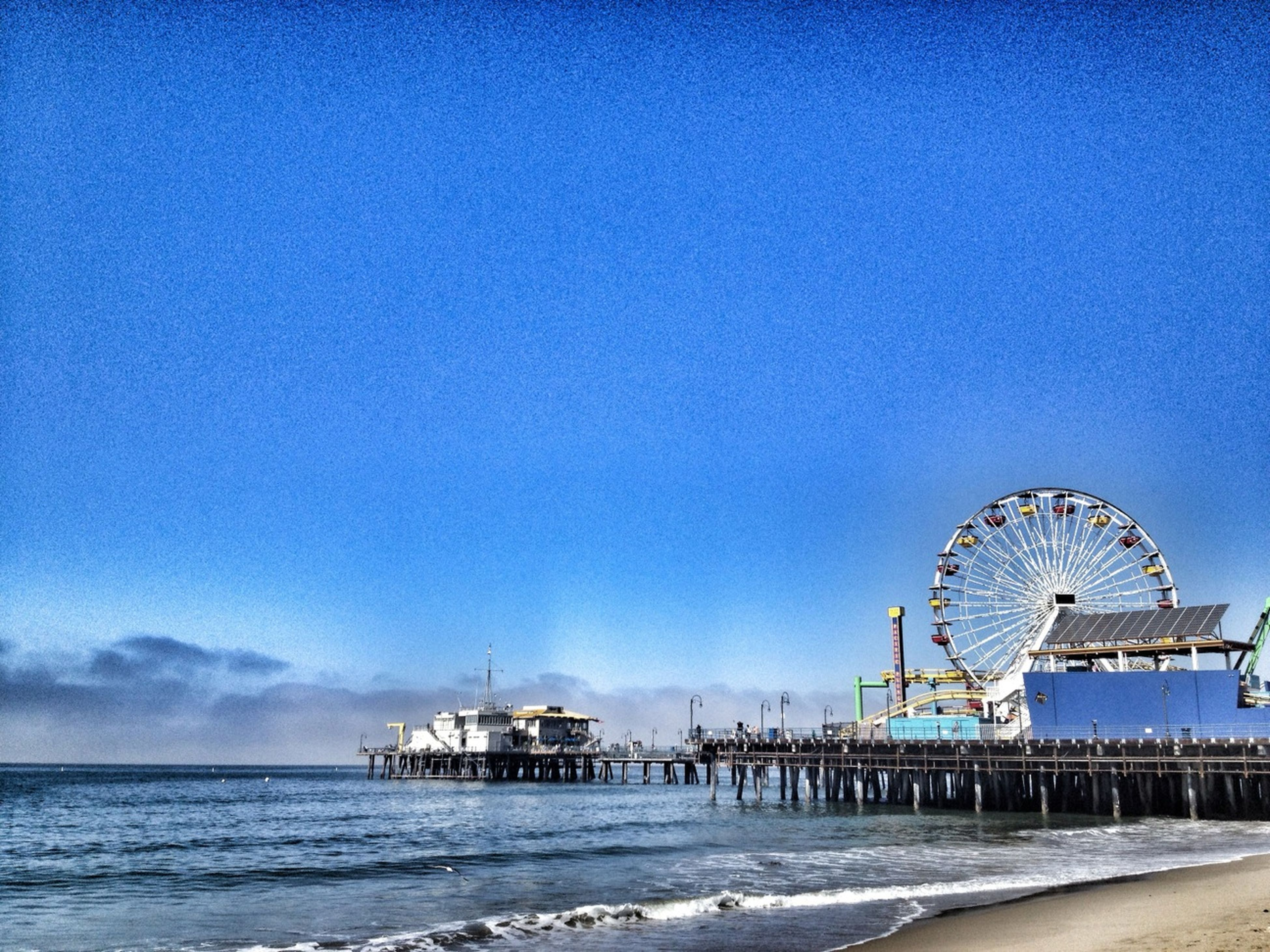 sea, water, beach, blue, horizon over water, sky, shore, sand, built structure, copy space, nautical vessel, tranquility, tranquil scene, transportation, clear sky, ferris wheel, architecture, scenics, nature, outdoors