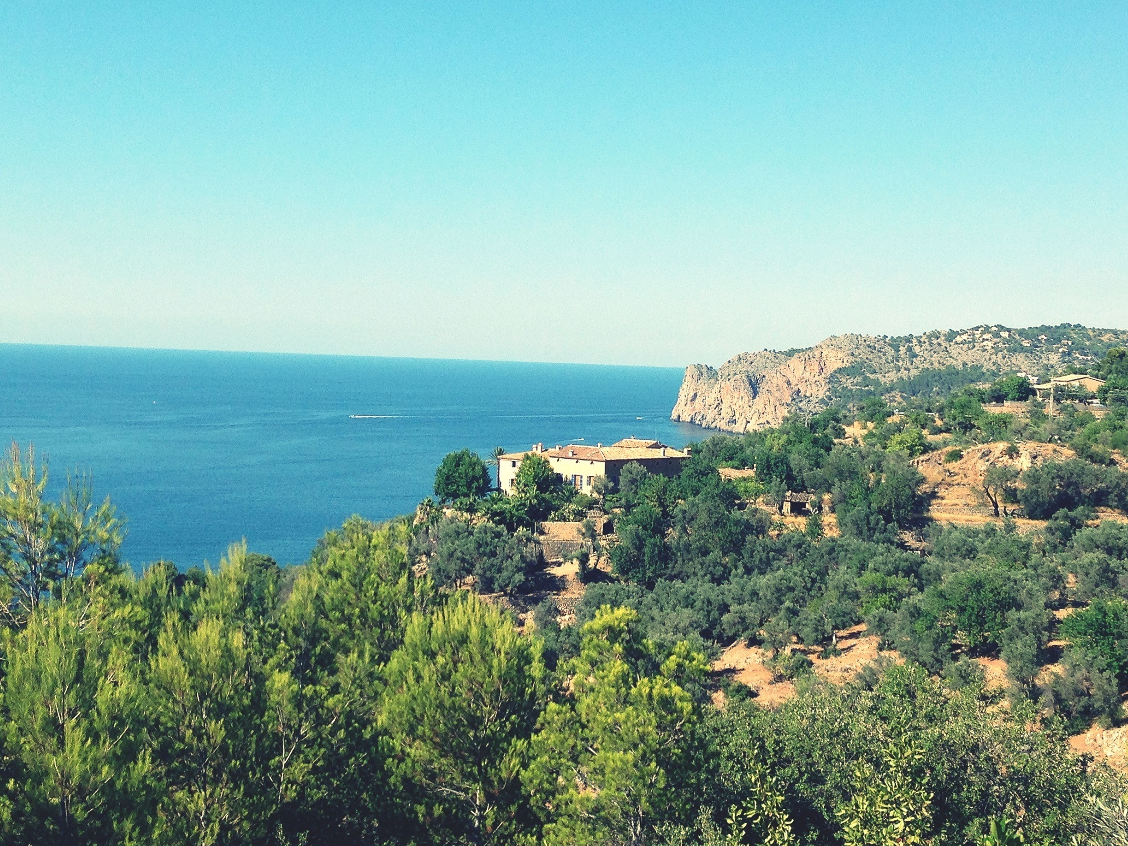 sea, clear sky, horizon over water, copy space, blue, water, tranquil scene, scenics, tranquility, beauty in nature, nature, cliff, high angle view, coastline, tree, idyllic, plant, rock formation, built structure, day