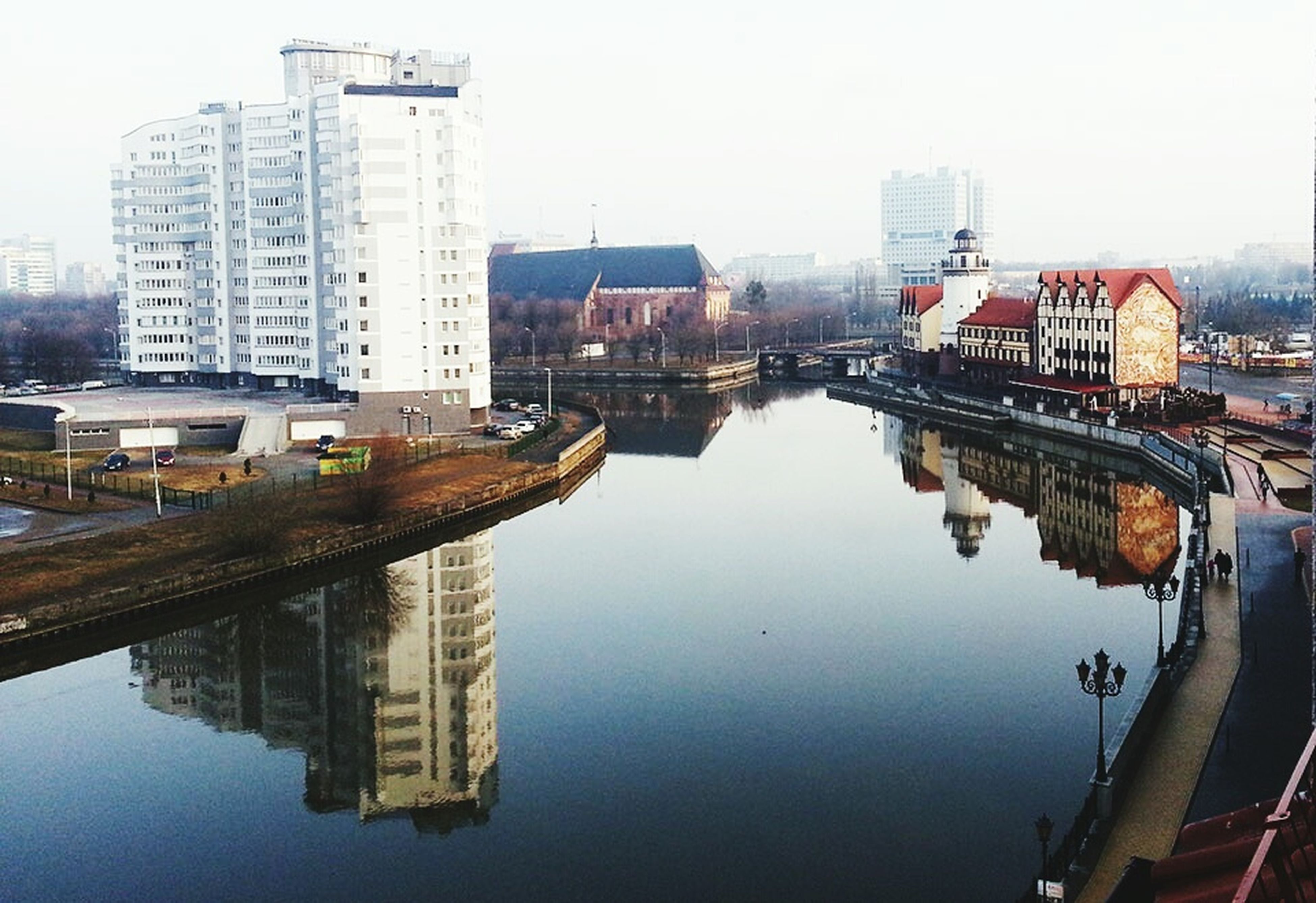 reflection, water, city, skyscraper, architecture, urban skyline, building exterior, river, modern, cityscape, built structure, waterfront, outdoors, bridge - man made structure, no people, sky, nautical vessel, downtown district, day