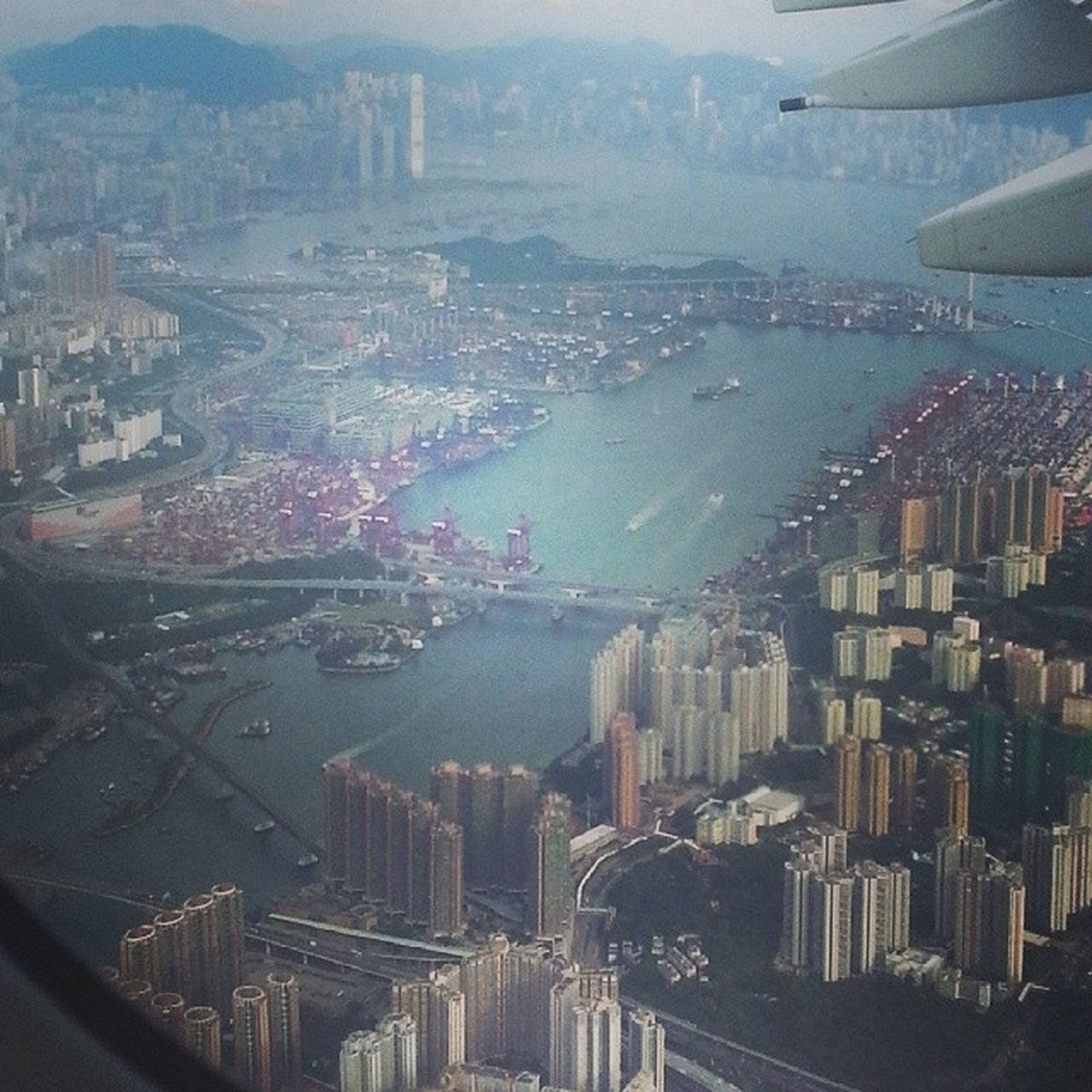 city, cityscape, building exterior, architecture, transportation, high angle view, aerial view, built structure, mode of transport, crowded, sea, water, city life, airplane, residential district, travel, river, flying, car, sky
